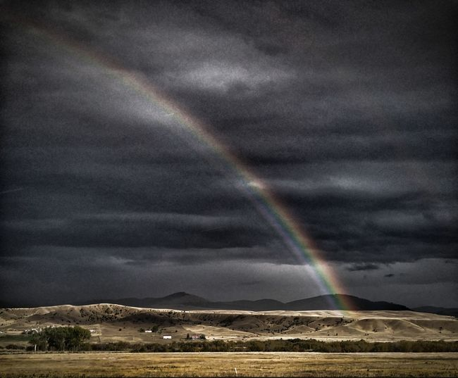 Dark Sky With Rainbow Driveby Shooting Rainbow Nature Weather Outdoors Scenics Double Rainbow Beauty In Nature Landscape . No People Mood Noire Natural Phenomenon Travel Destinations Mountain Spectrum Day Water Sky