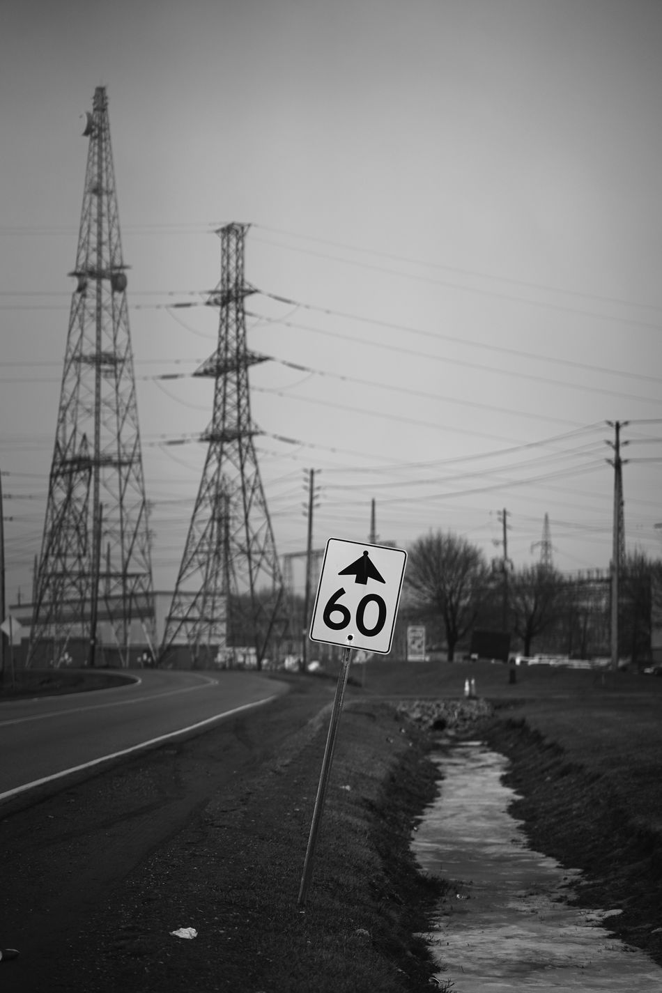 speed limit Cable Communication Connection Day Ditching Class Electricity Pylon Grass Grassy Monochrome No People Outdoors Powerlines Road Sky Speed Sign Wires