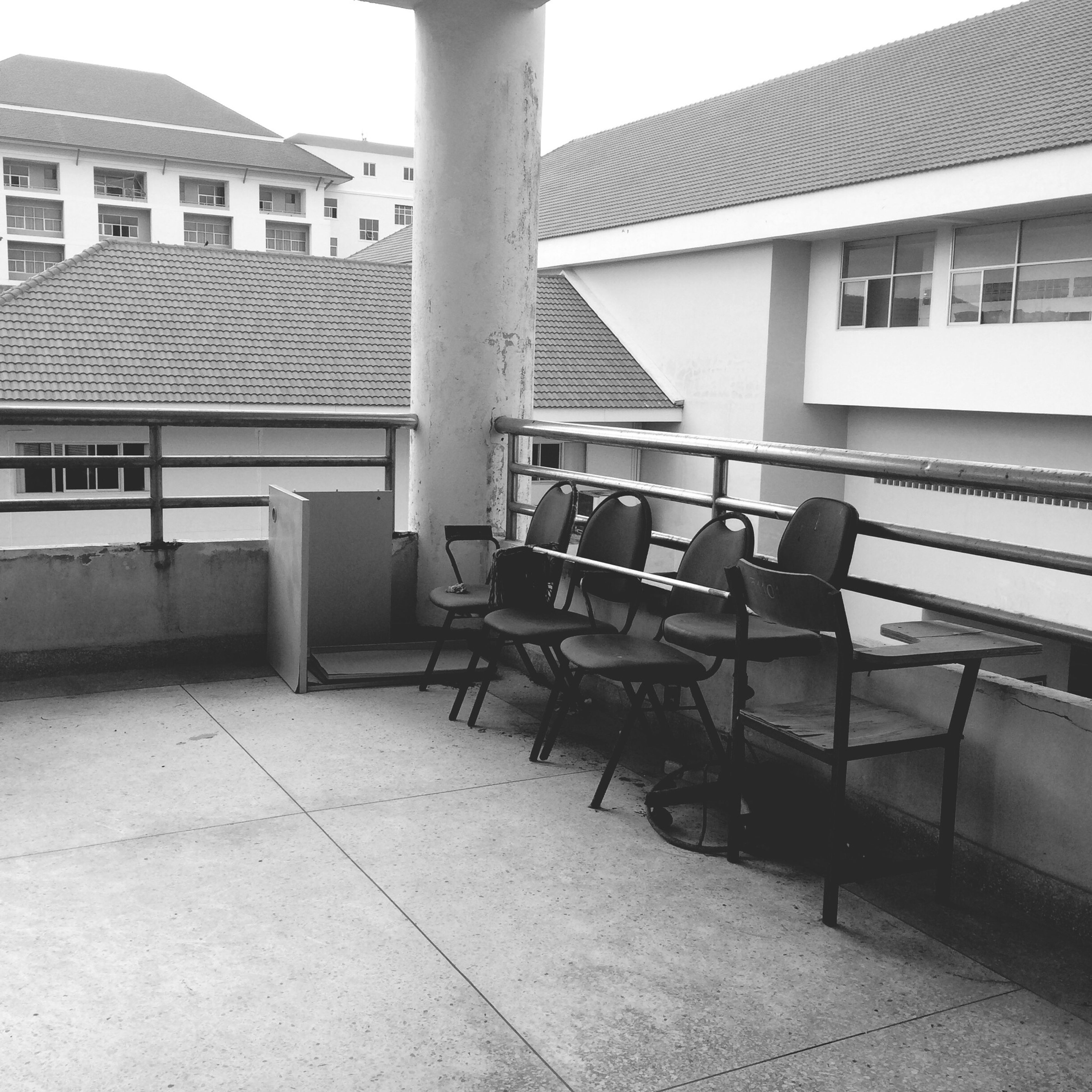 architecture, built structure, building exterior, chair, empty, absence, building, sunlight, railing, city, residential building, residential structure, day, house, bench, window, no people, balcony, outdoors, shadow