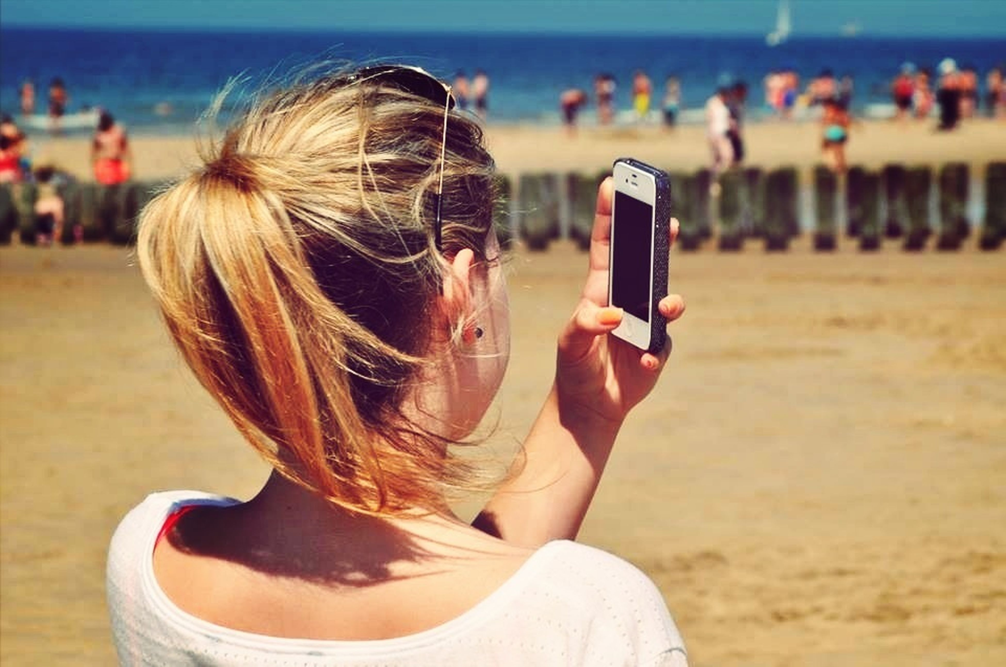 focus on foreground, beach, lifestyles, leisure activity, sea, water, sand, person, shore, headshot, rear view, blond hair, incidental people, childhood, girls, vacations, close-up