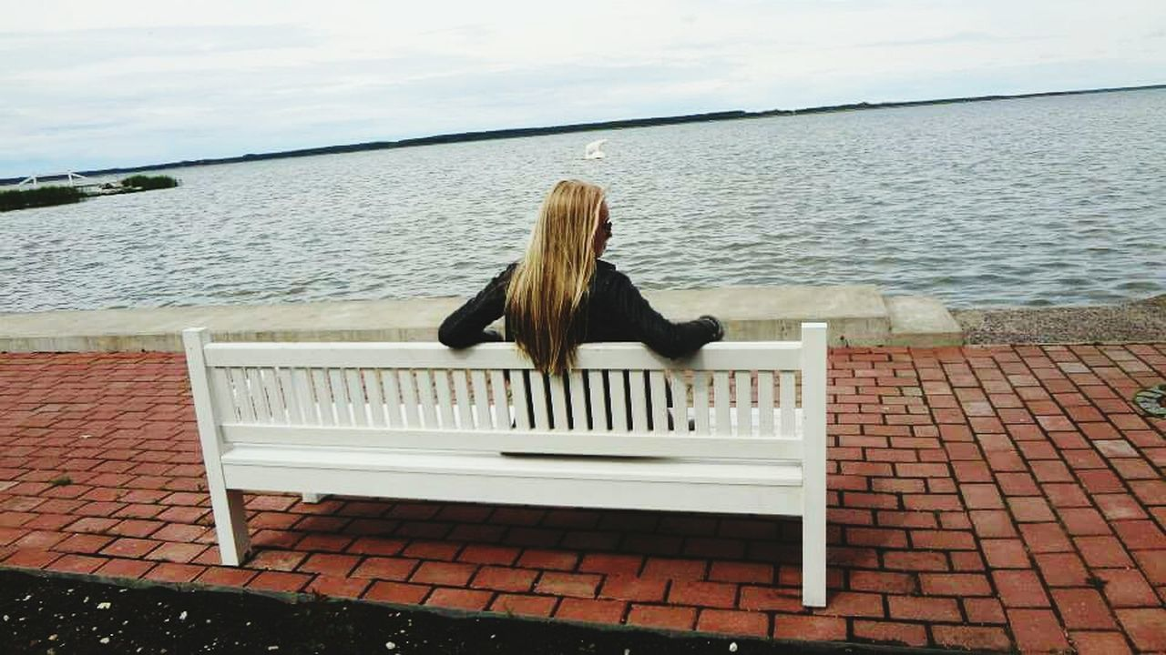 water, one person, real people, sitting, rear view, sea, day, leisure activity, outdoors, sky, nature, lifestyles, young women, relaxation, horizon over water, women, young adult, blond hair, beauty in nature, people