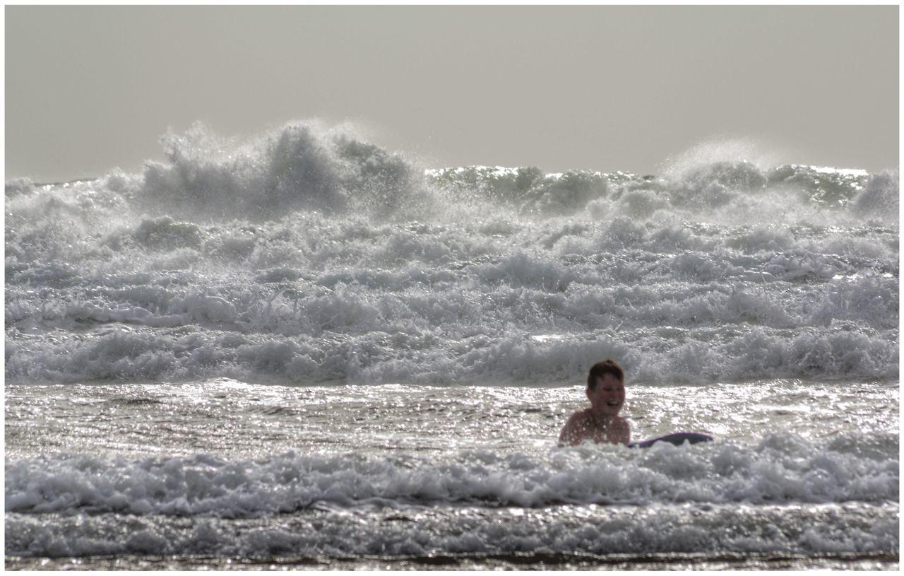 Boy Enjoying In Sea Against Sky