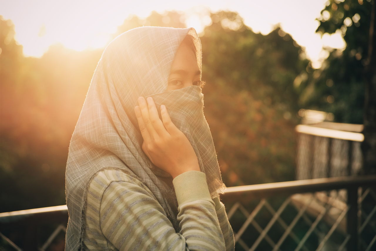 Close-Up Of Young Woman Covering Face With Scarf