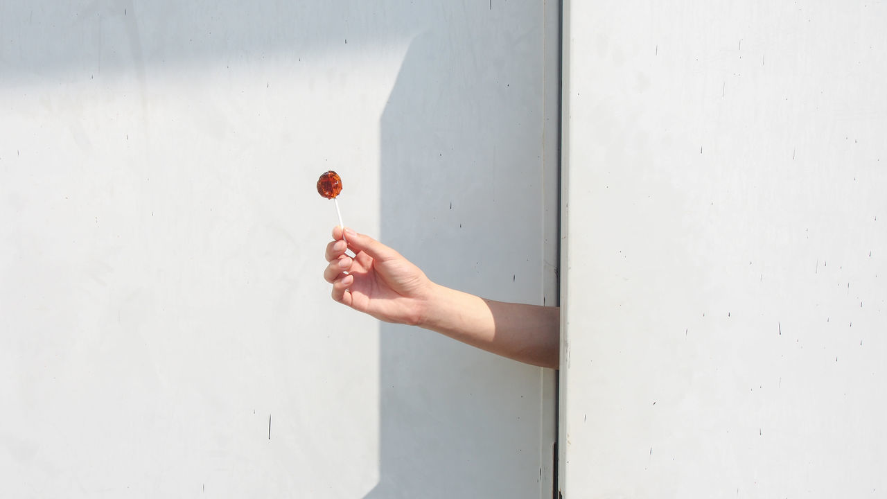 Cheer you up from nowhere. A hand offers a candy through doors. Abstract Backgrounds Candy Day Delivery Doors Fingers Gap Give Hide Holding Human Body Part Human Hand Minimalist Architecture Offering Open Peeking Sweet The City Light Wall White Fresh On Market 2017