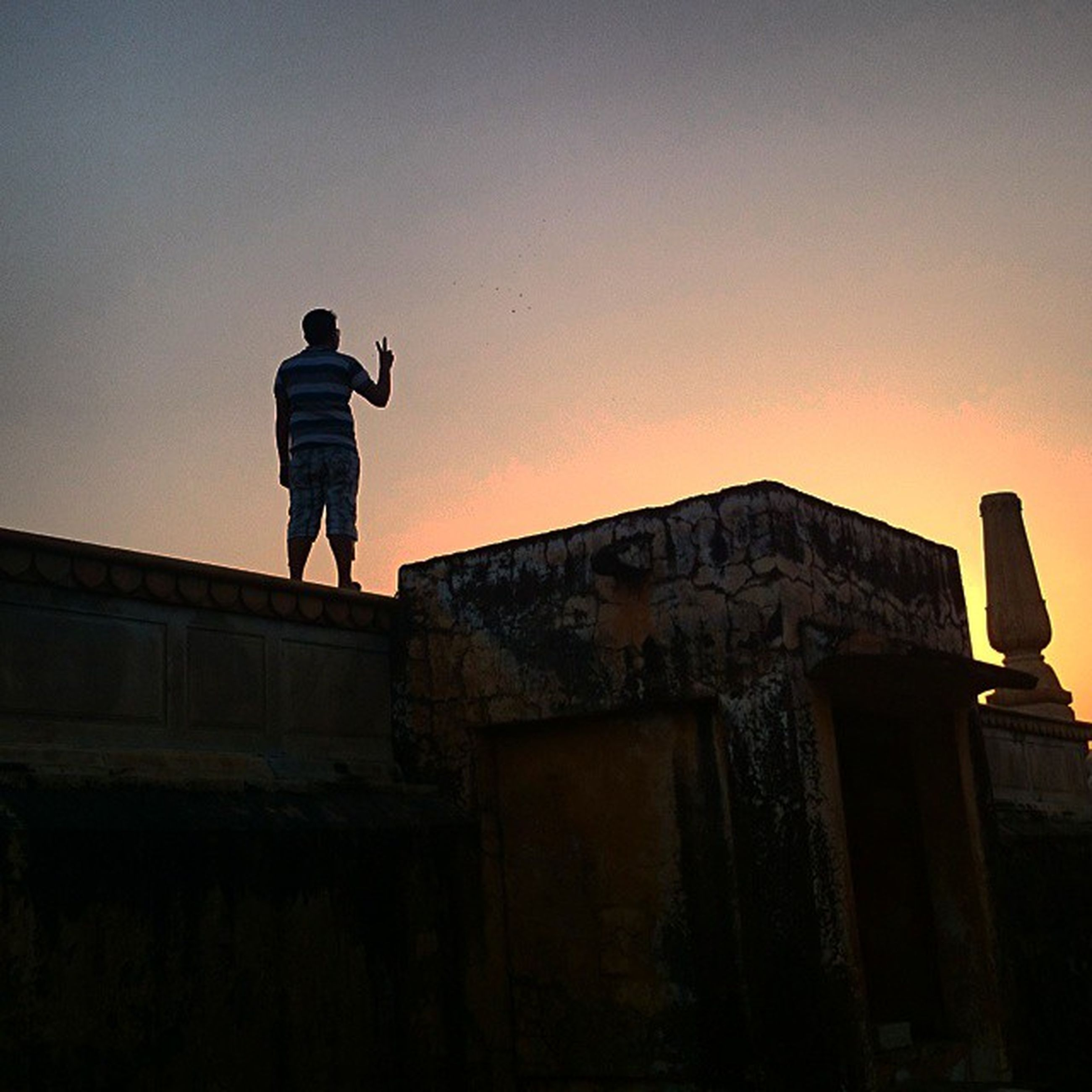 architecture, full length, built structure, building exterior, lifestyles, standing, copy space, leisure activity, clear sky, men, low angle view, casual clothing, silhouette, sunset, sky, rear view, walking, outdoors