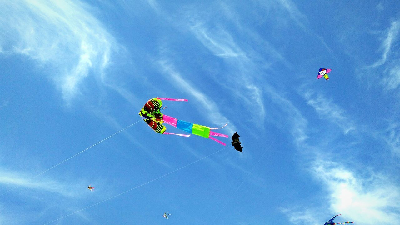 low angle view, sky, flying, mid-air, day, multi colored, kite, fun, cloud - sky, leisure activity, kite - toy, outdoors, adventure, real people, blue, nature, parachute, beauty in nature