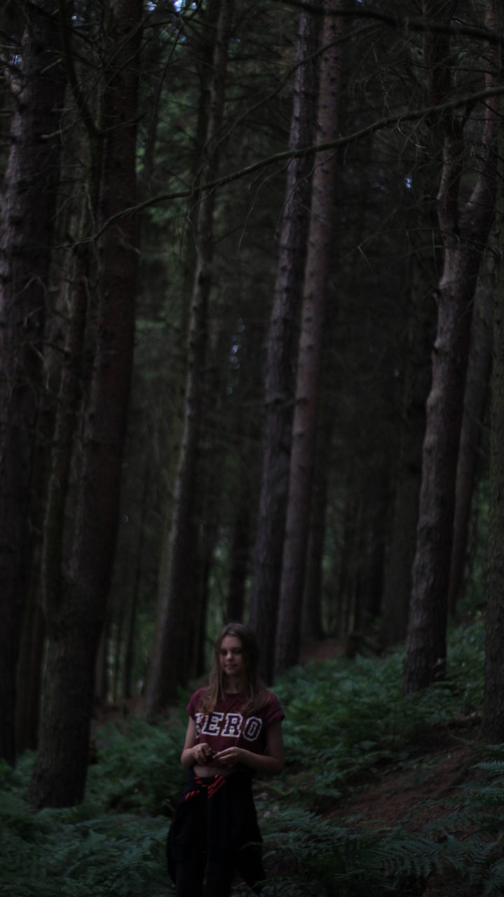 Girl Standing On Field Against Trees At Forest