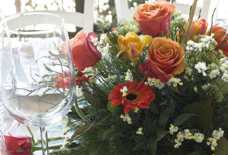 Close up of a floral bouquet as a centrepiece on a table Bouquet Bouquet Of Flowers Centerpiece Centrepiece Close-up Day Flower Flower Head Flowers Freshness Glass No People Orange Rose Outdoors Red Rose Roses Wedding