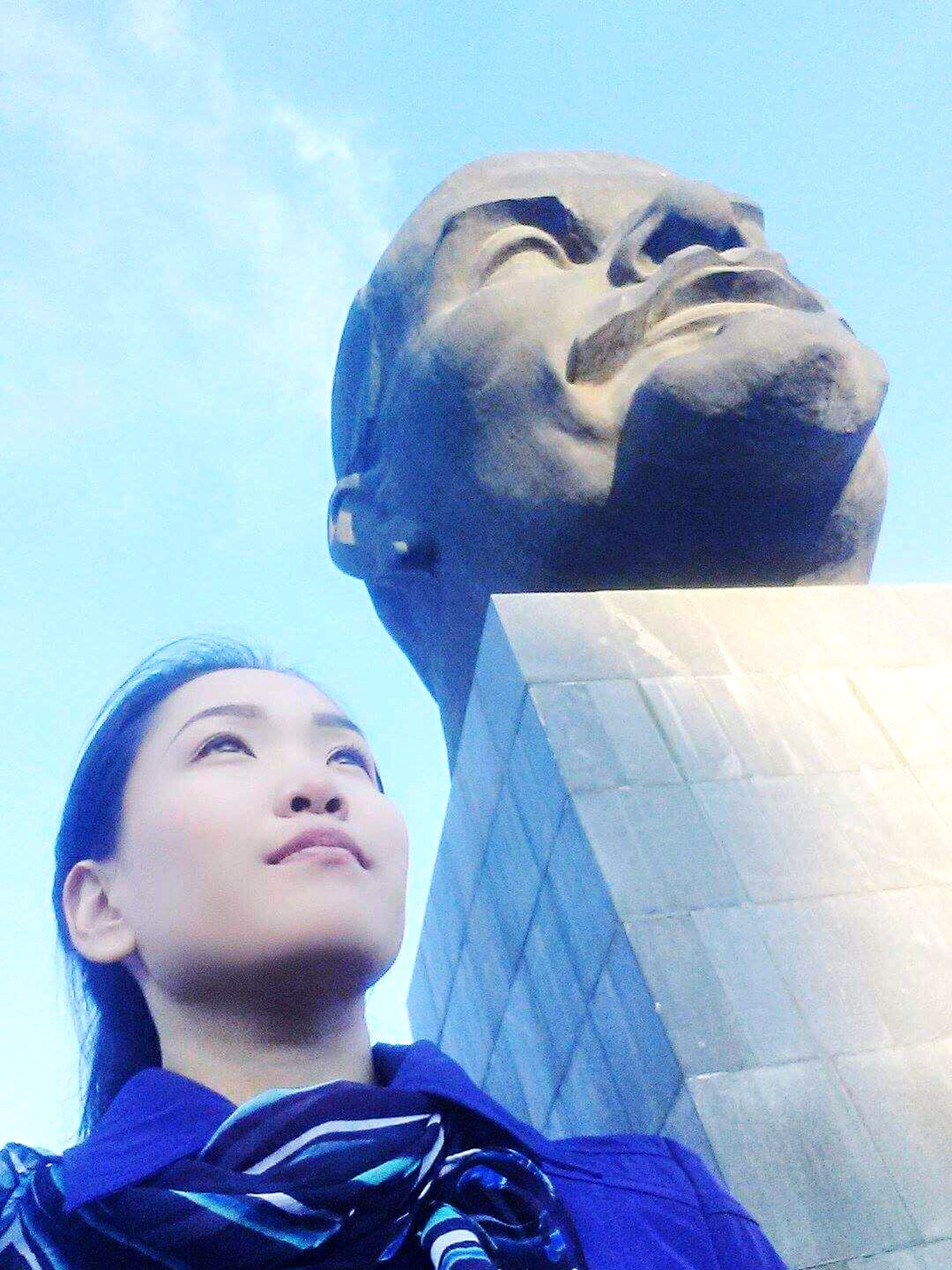 sky, business, women, low angle view, togetherness, human face, city, love, two people, cloud - sky, statue, outdoors, friendship, young women, men, corporate business, day, young adult, close-up, adult, people