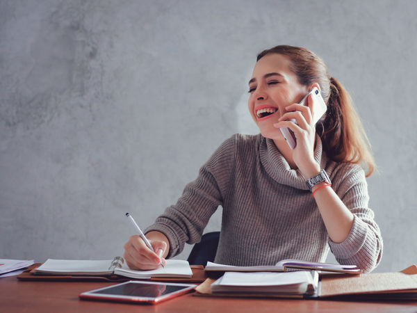 Answering Business Businesswoman Communication Connection Desk Holding Listening Mobile Phone Occupation One Person One Young Woman Only Pen Sitting Smiling Talking Technology Telephone Using Phone Wireless Technology Women Working Writing Young Adult Young Women