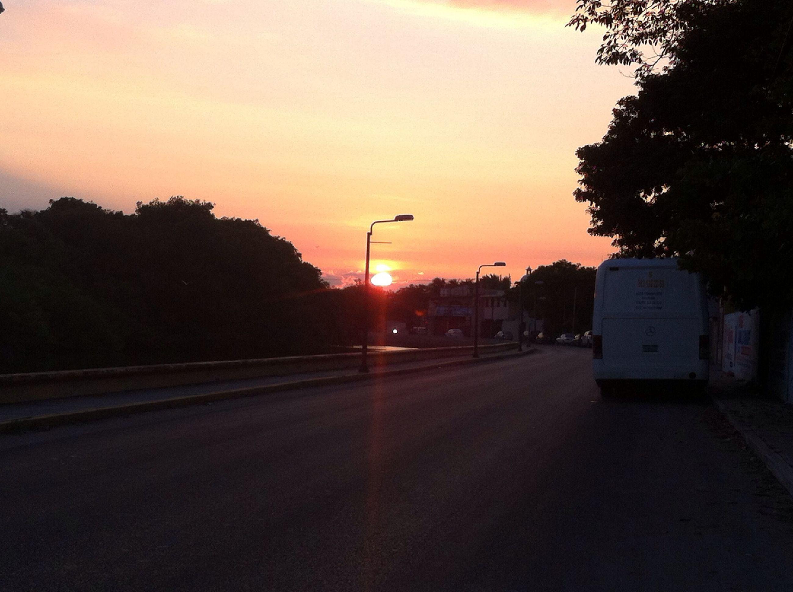 sunset, transportation, road, the way forward, tree, silhouette, street light, street, sky, orange color, car, diminishing perspective, road marking, empty, illuminated, vanishing point, no people, outdoors, nature, dusk