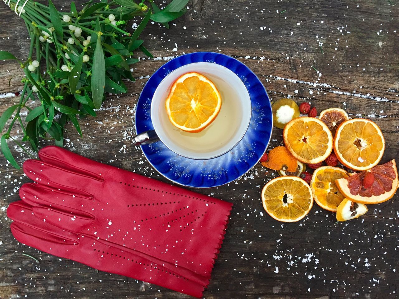 Red gloves near a mug of orange tea with dried orange slices beside and mistletoe on snowy table Lemon Table High Angle View Refreshment Freshness Drink Day Winter Snow Cold Gloves Red Gloves Table Snowy Mistletoe Drink Cup Glass Tea Slices Oranges