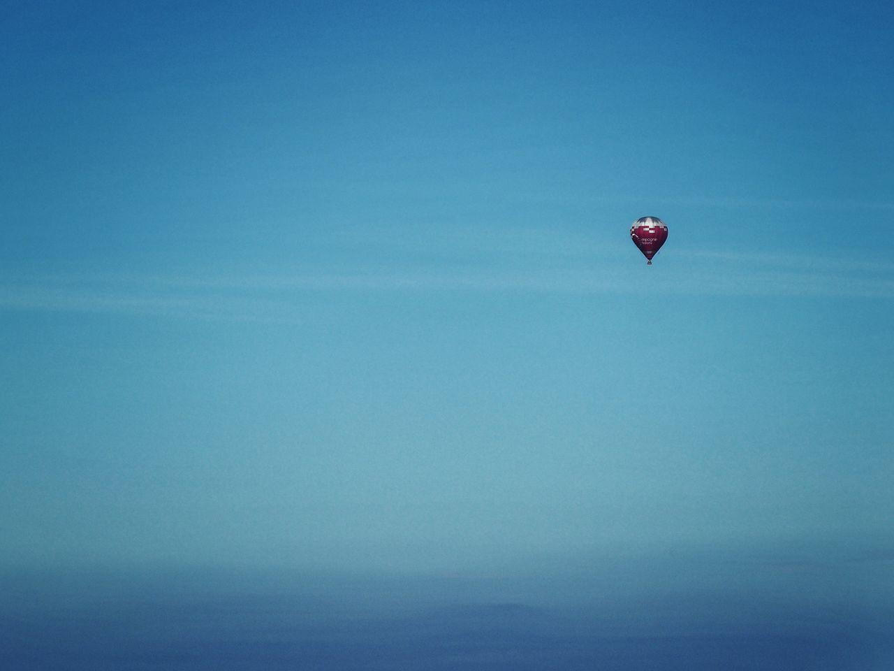 mid-air, flying, parachute, day, nature, sea, adventure, clear sky, outdoors, sky, beauty in nature, no people, hot air balloon, paragliding