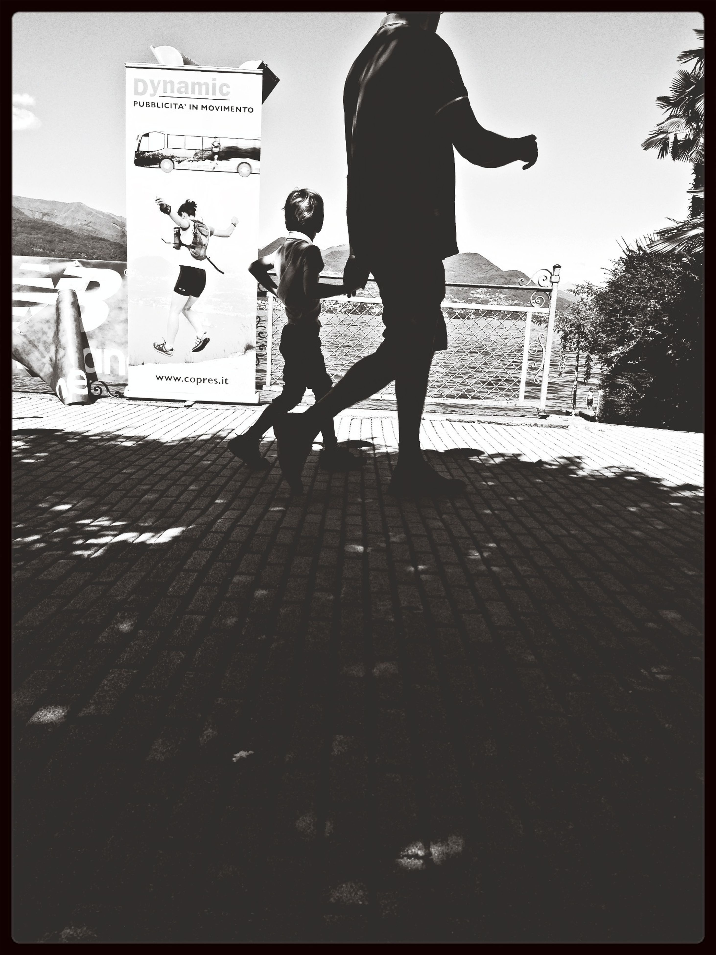 transfer print, auto post production filter, lifestyles, walking, leisure activity, full length, men, shadow, clear sky, person, silhouette, standing, sunlight, street, rear view, childhood, outdoors