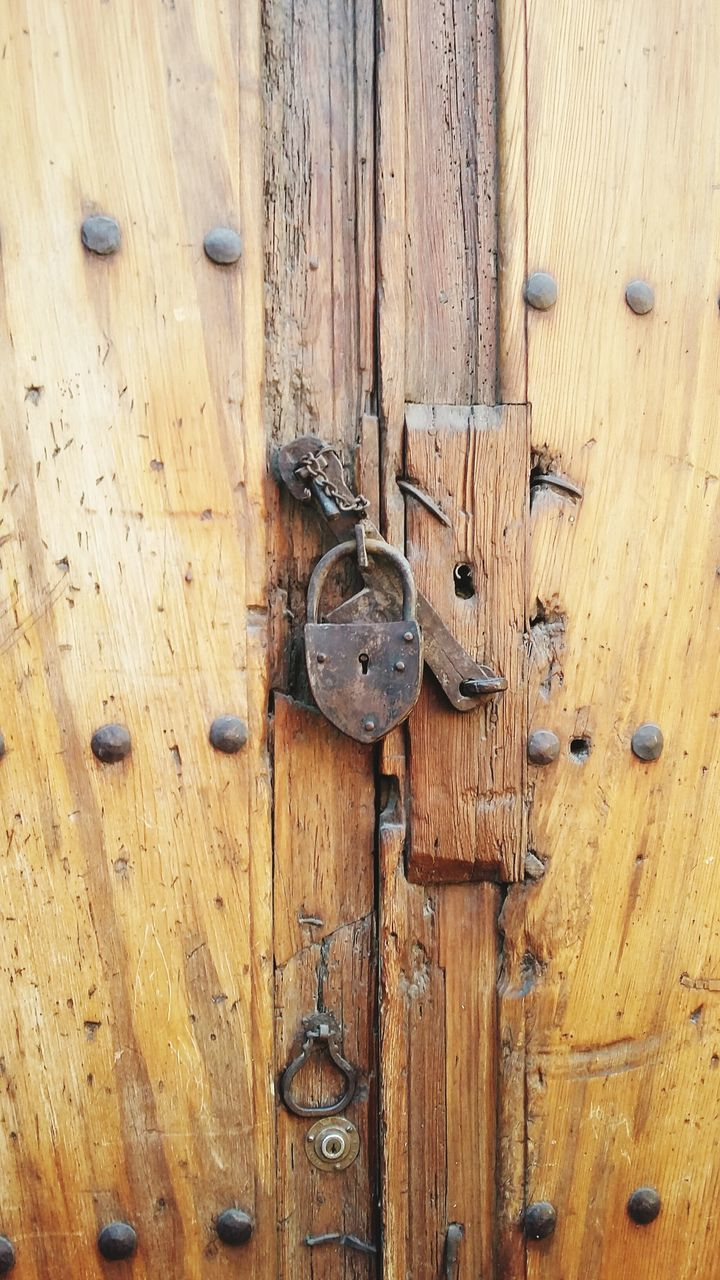 Close-Up Of Old-Fashioned Padlock On Wooden Door