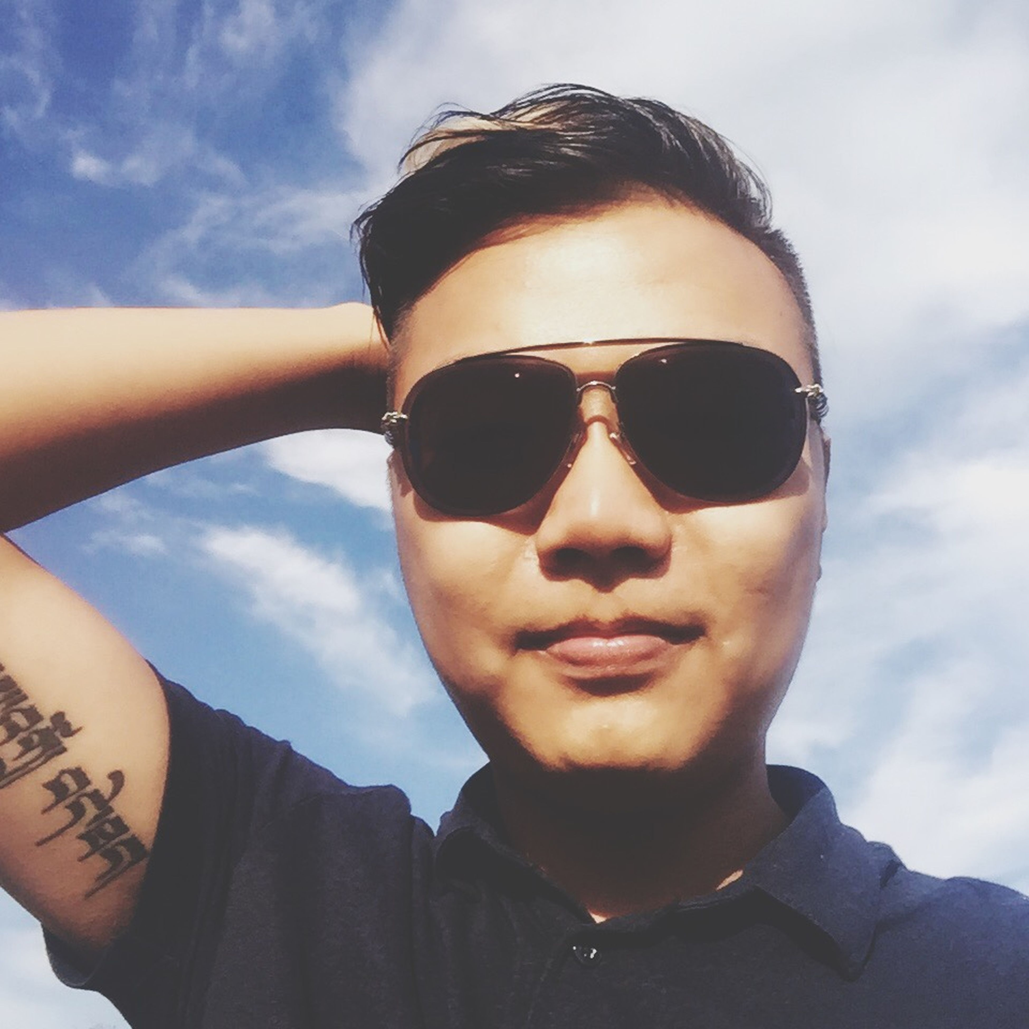 looking at camera, portrait, sky, lifestyles, person, headshot, sunglasses, leisure activity, young adult, front view, cloud - sky, young men, smiling, cloud, head and shoulders, close-up, day, mid adult