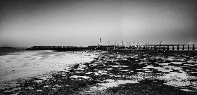 Water Pier Sea Beach Built Structure Shore Sand Scenics Tranquil Scene Tranquility Nature Day Sky Outdoors Beauty In Nature No People Waterfront The Way Forward Seascape Surface Level Non-urban Scene Tranquility Black And White Vacations Tourism