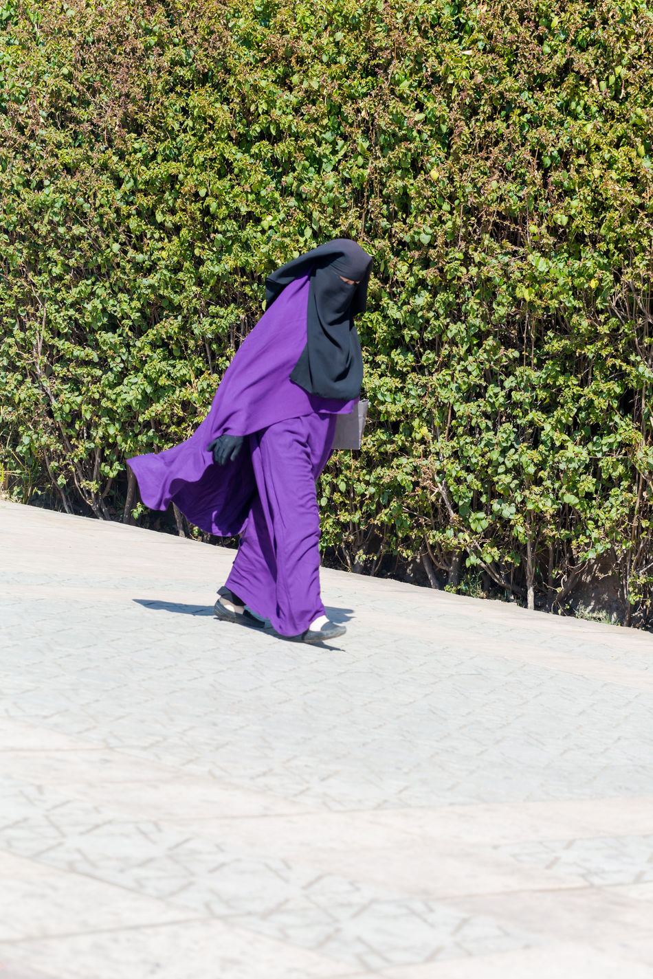 Islamic Muslim woman wearing violet black Niqab walks on Marrakesh street. 15 February 2017 Abaya Adults Only Alienation Assertion Chador Culture Difference  Green Color Hijab Iconic Islam Jilbab Lifestyle Marrakech Migrant Muslim One Woman Only Only Women Oppression Real People Religion And Beliefs Seperation Street Traditional Clothing Violet