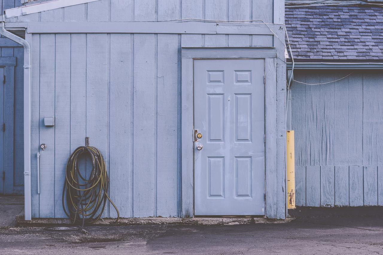 Blue Blue Wall Building Building Exterior Door Entrance Entry Exterior Wall Hose Hoses Parking Lot Shingles Wall Pastel
