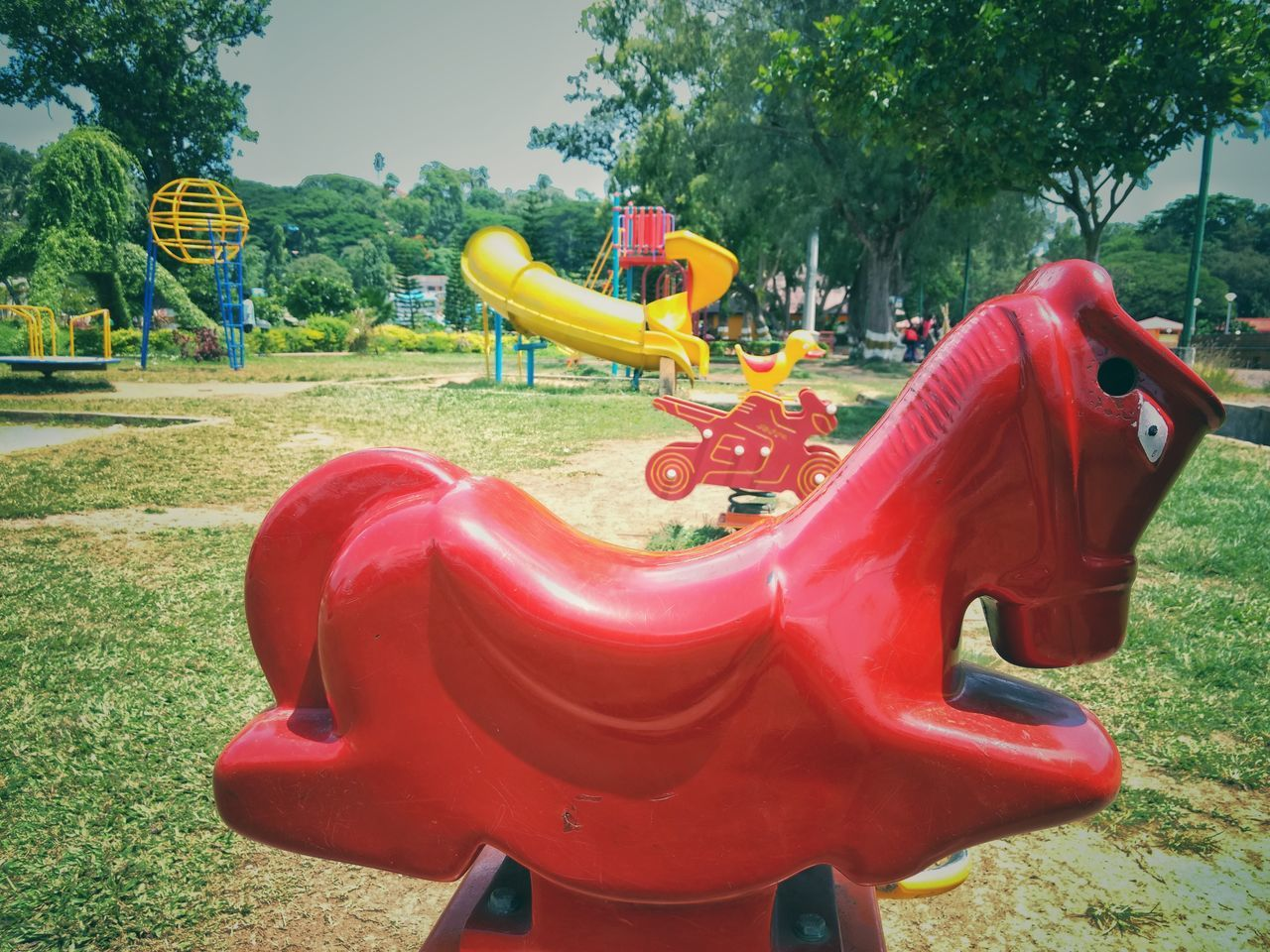 playground, outdoor play equipment, childhood, tree, park - man made space, red, slide, absence, empty, day, water park, amusement park, no people, outdoors, fun, water slide, merry-go-round, carousel, nature