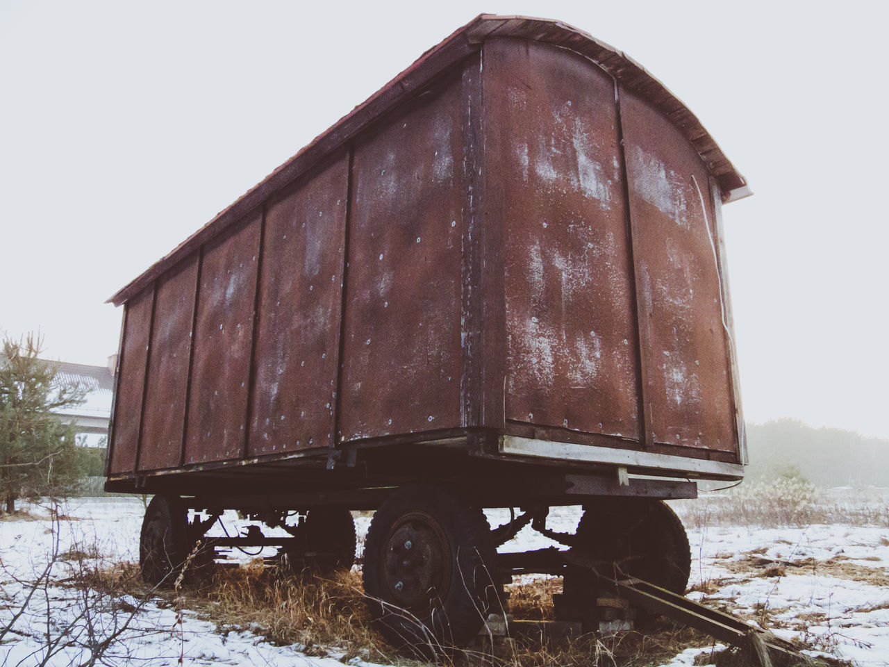 Low angle view of an old wagon standing in the field in winter. Cart Circus Covered Wagon Freight Transportation Obsolete Old Old-fashioned Outdoors Plank Retro Styled Rural Scene Transportation Travel Wagon  Wheels Wood