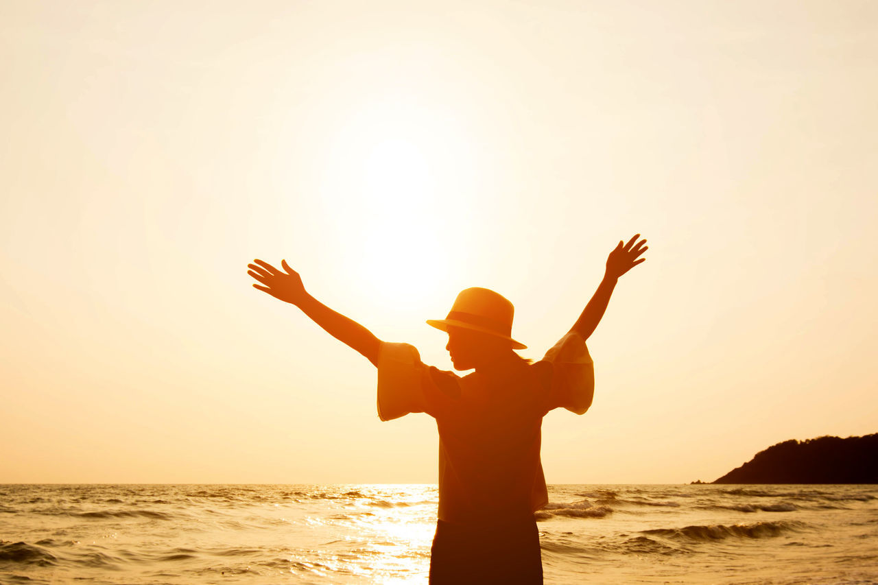 Rear View Of Woman With Arms Outstretched By Sea Against Clear Sky During Sunset
