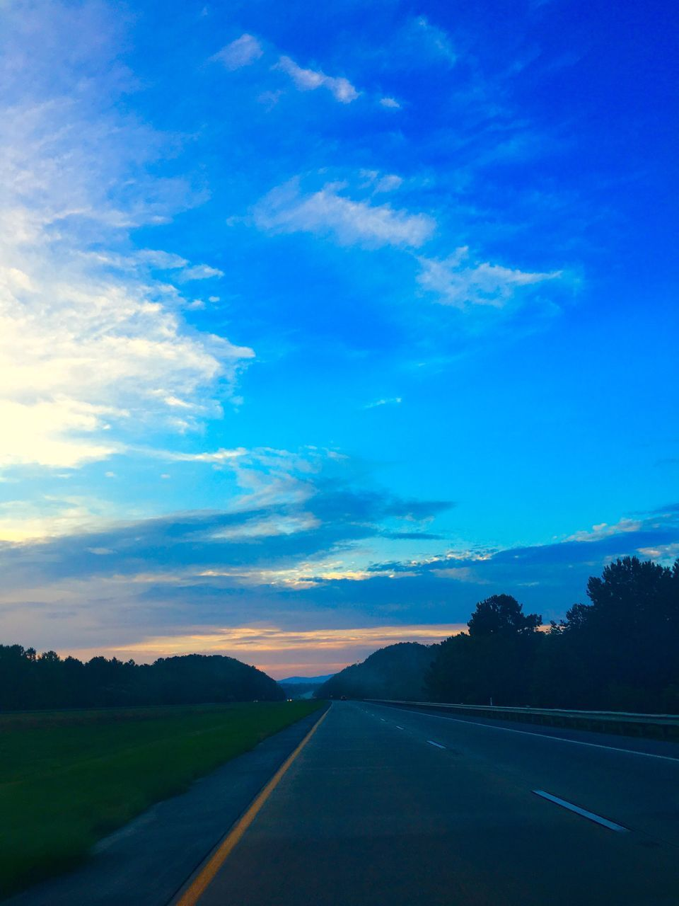 road, the way forward, sky, transportation, road marking, blue, tranquil scene, landscape, nature, scenics, tranquility, outdoors, dividing line, no people, beauty in nature, sunset, day, tree