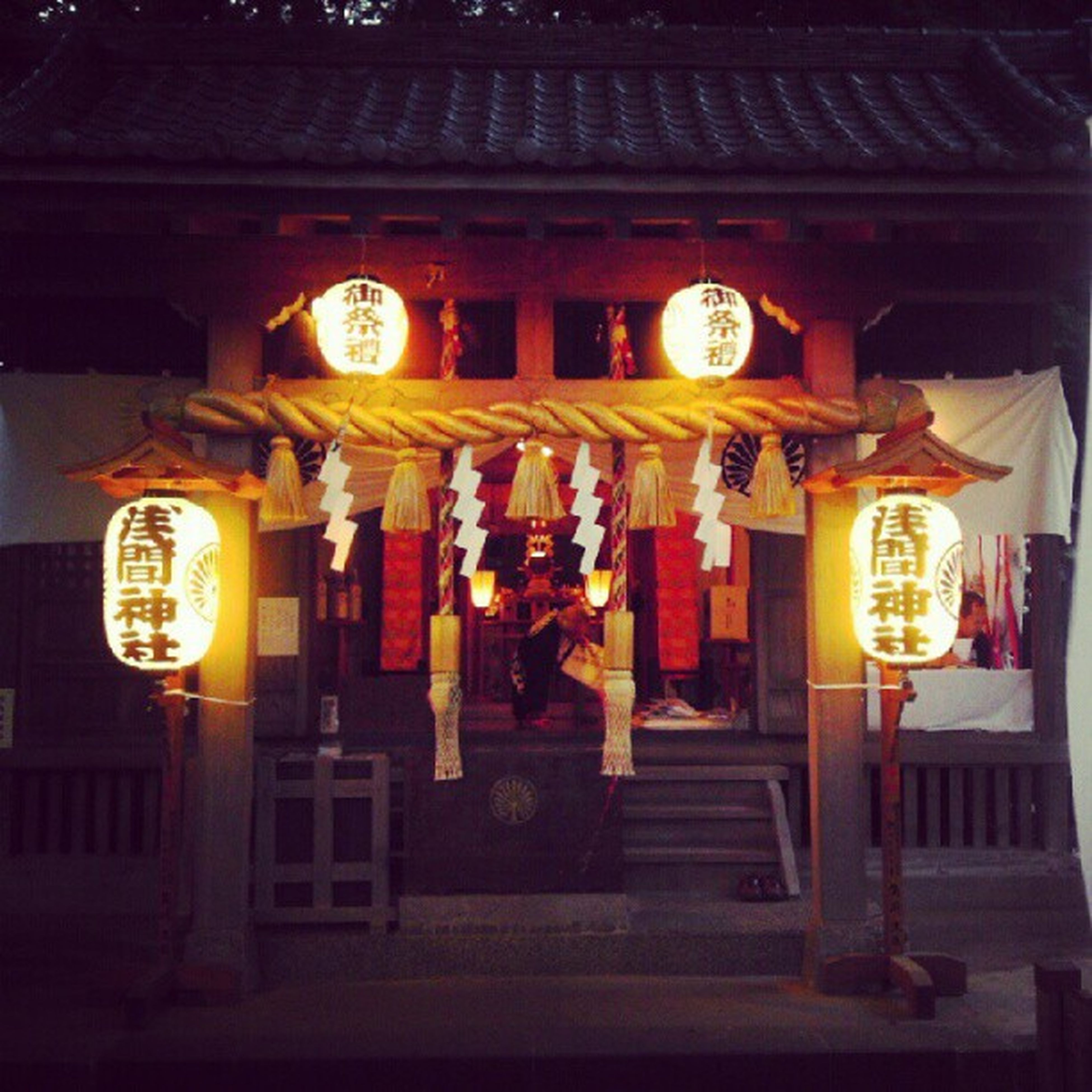 illuminated, night, text, lantern, lighting equipment, non-western script, architecture, built structure, building exterior, western script, religion, communication, place of worship, hanging, decoration, store, spirituality, low angle view, tradition, yellow
