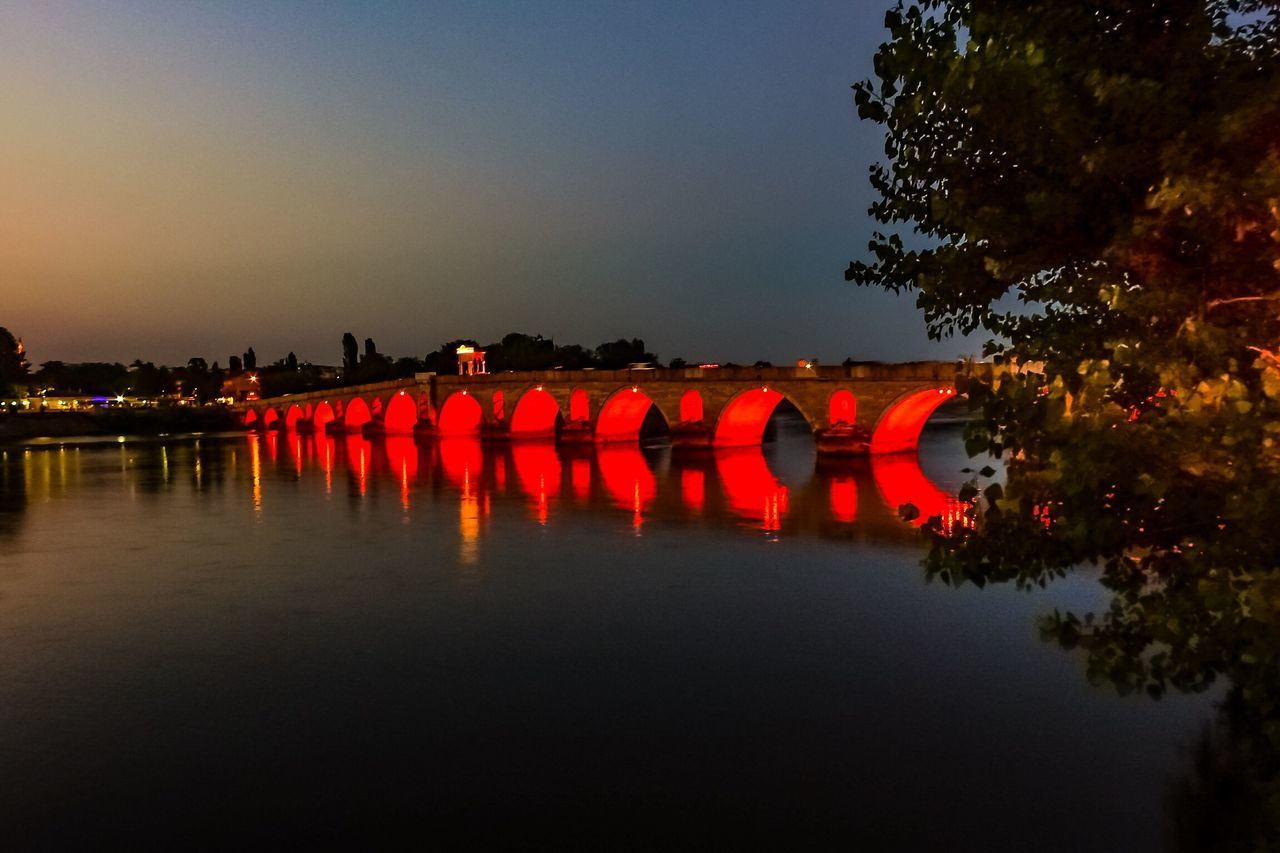 orange color, river, reflection, waterfront, water, bridge - man made structure, tree, outdoors, red, sunset, sky, illuminated, nature, architecture, large group of people, day