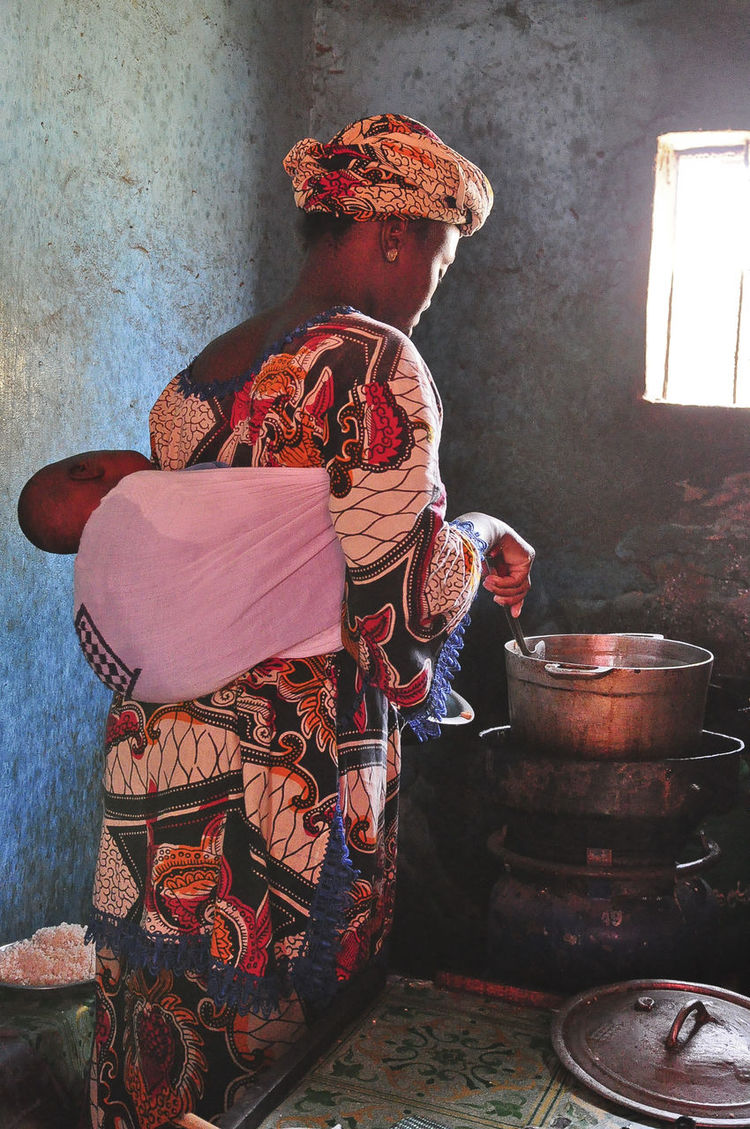 Cooking at the roadside cafe African Mother And Child Cooking Indoors  Mother And Baby Rear View Roadside Cafe Rural Africa Standing