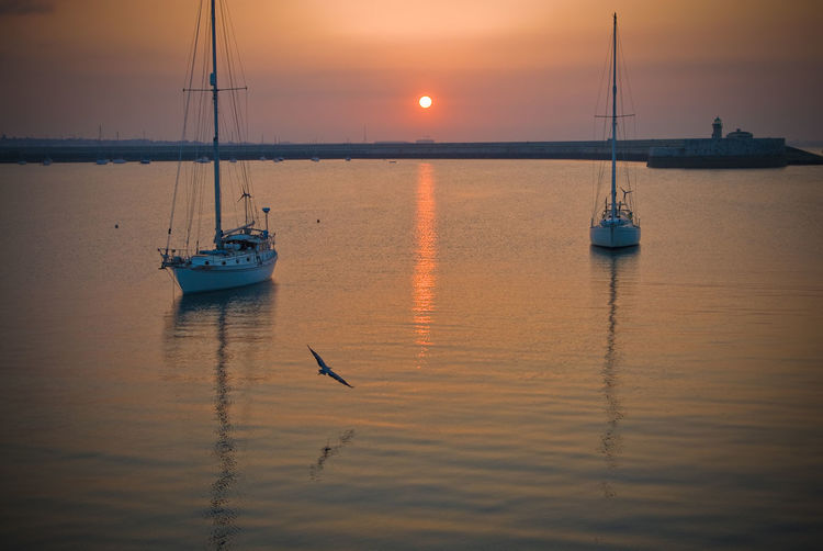 A Quiet Sunset in DunLaoghaire Harbour. Boats Boats And Moorings Boats⛵️ Dunlaoghaire Harbour Harbour View Harbour Wall Lighthouse Low Flying Birds Maritime Masts Orange Orange Sky Pier Reflection Reflection_collection Sailboat Sailing Sea Birds Seagull Sunset Sunset_collection Tranquil Scene Pastel Power