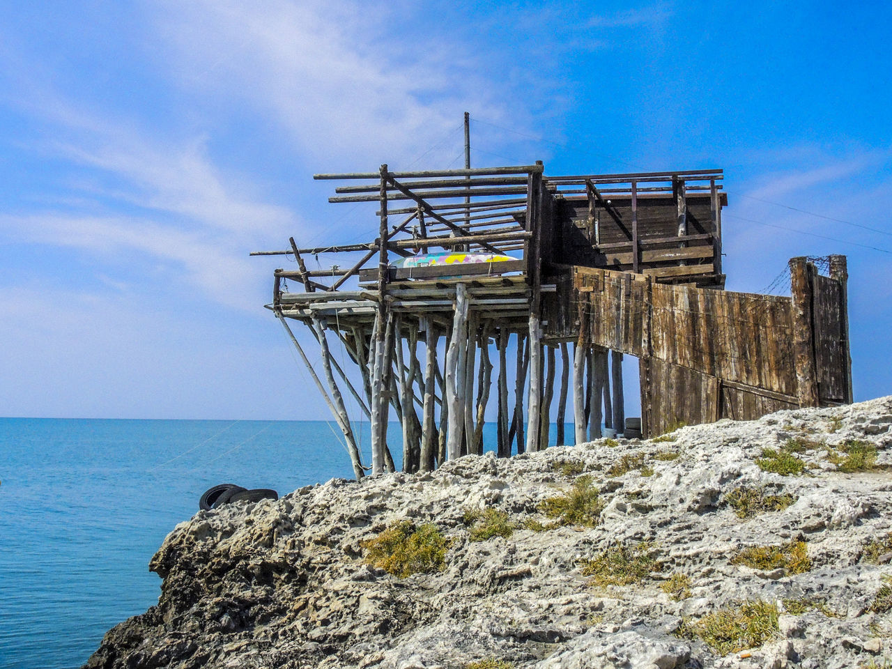 Built Structure By Sea Against Blue Sky