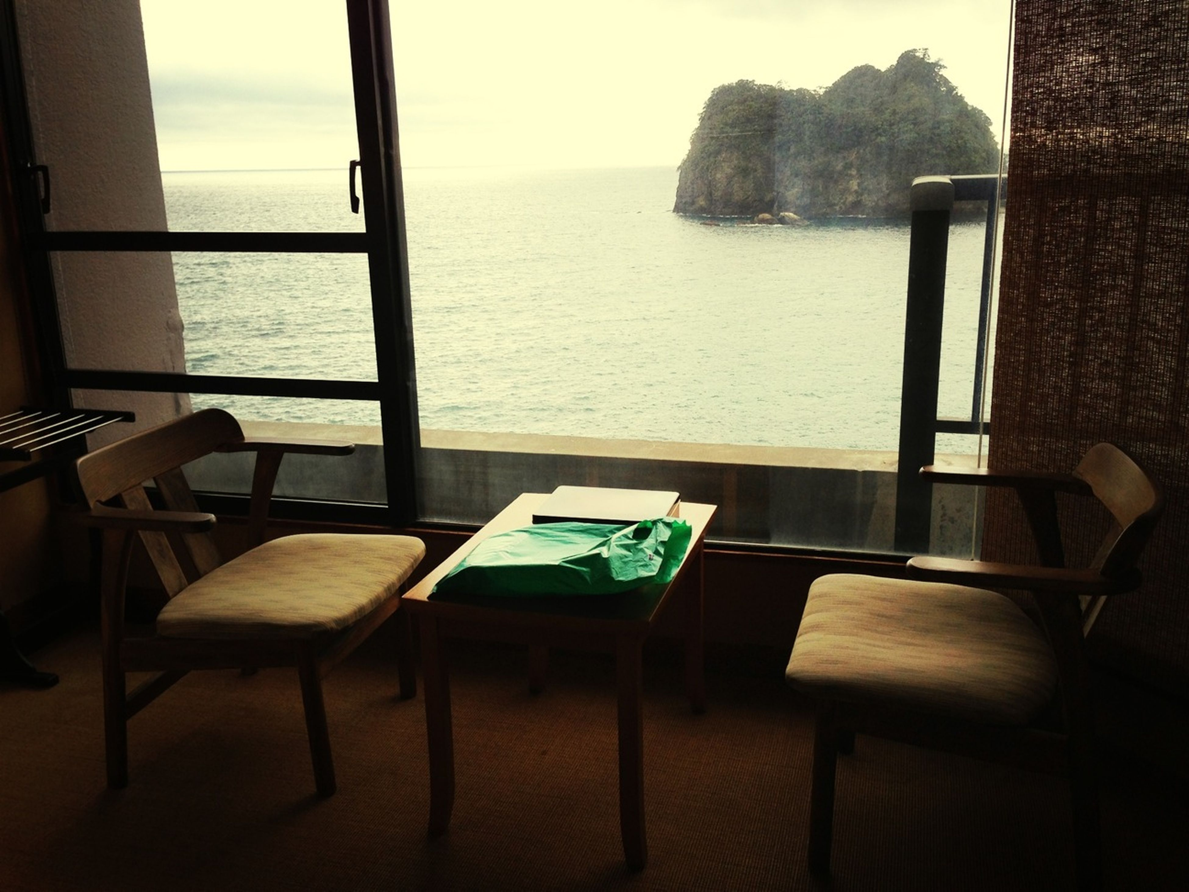 chair, table, absence, empty, sea, water, indoors, seat, furniture, relaxation, place setting, restaurant, tranquility, deck chair, tranquil scene, day, sunlight, no people, window, wood - material