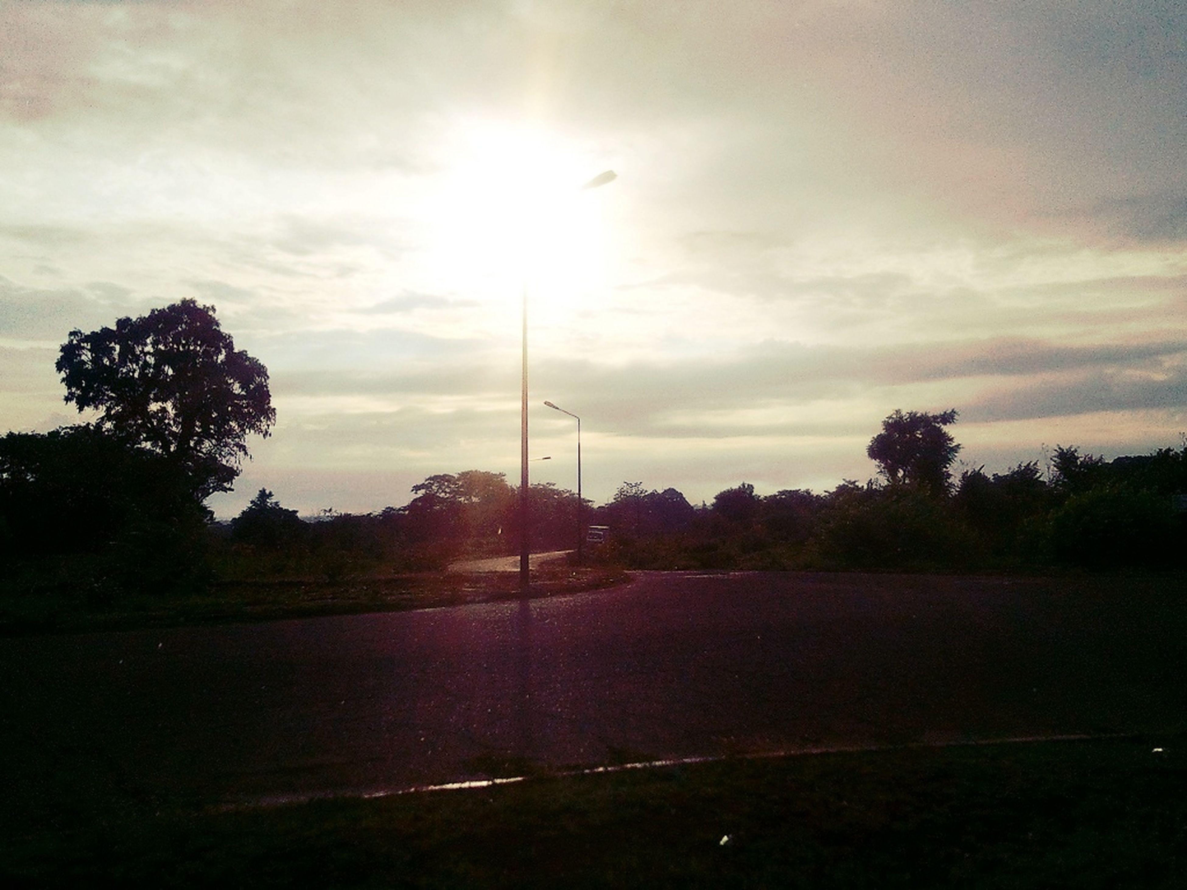 tree, sky, cloud - sky, sun, tranquility, tranquil scene, scenics, nature, beauty in nature, silhouette, sunset, sunlight, cloudy, landscape, field, cloud, sunbeam, grass, street light, road