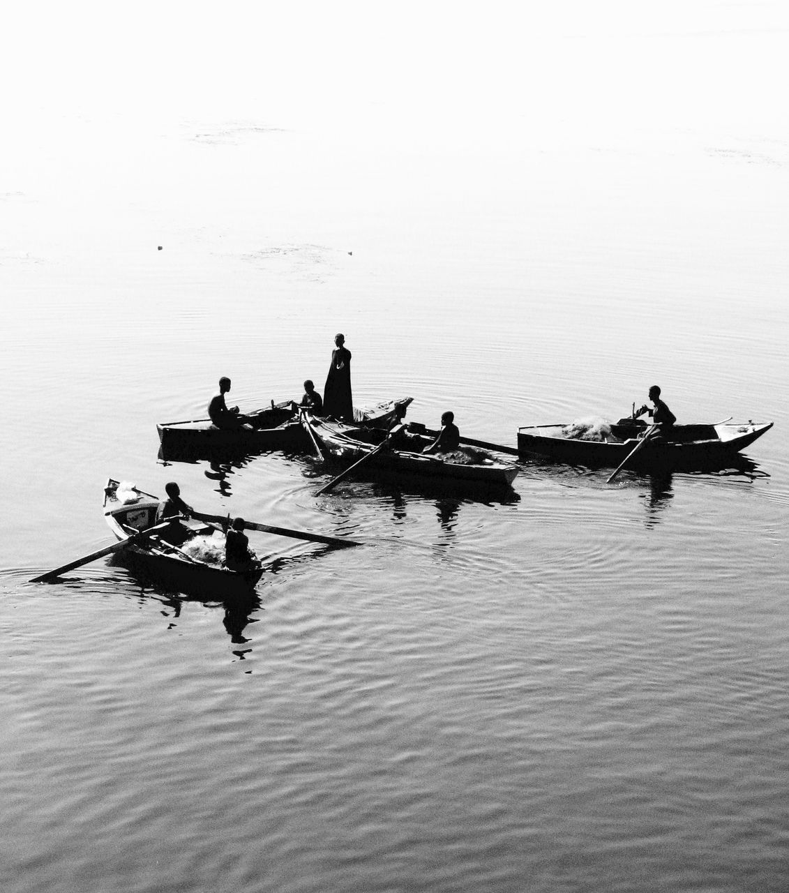 nautical vessel, transportation, mode of transport, water, rowing, oar, men, real people, silhouette, nature, outdoors, occupation, day, rowboat, teamwork, beauty in nature, sailing, longtail boat, gondola - traditional boat, one person, sky, people