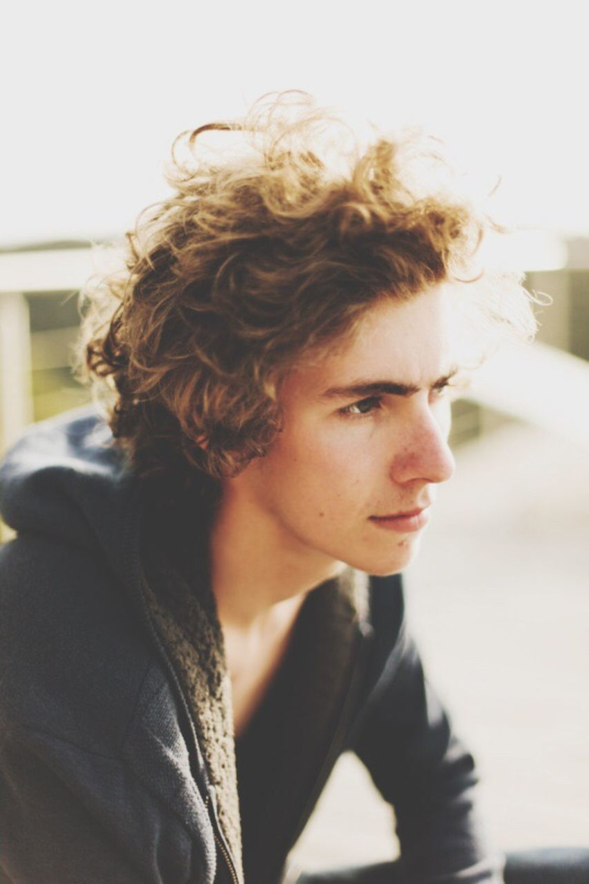 young adult, contemplation, focus on foreground, one person, young men, real people, young women, indoors, curly hair, lifestyles, close-up, day, portrait, blond hair, people