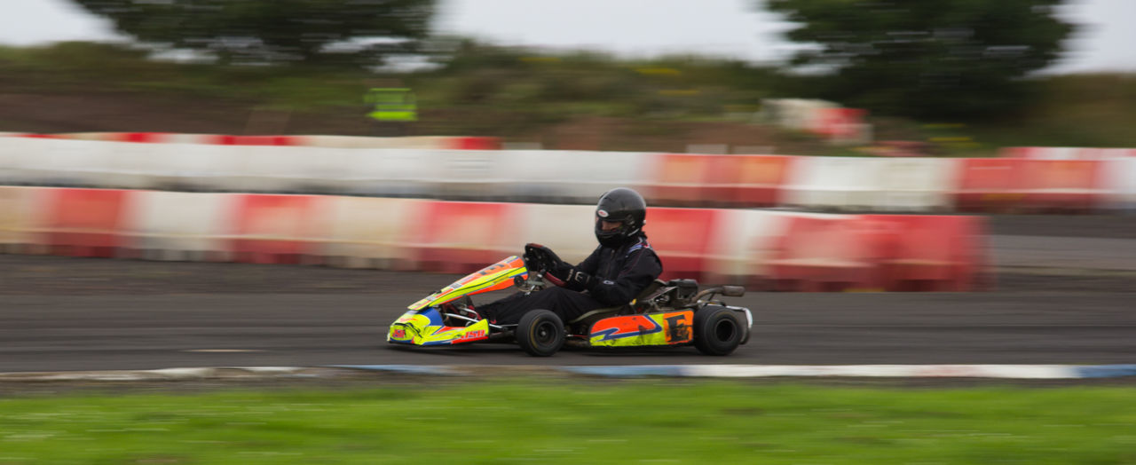 speed, blurred motion, sports race, motorsport, real people, motion, land vehicle, transportation, mode of transport, men, outdoors, competition, day, two people, sports clothing, competitive sport, sports track, sport, racecar, people