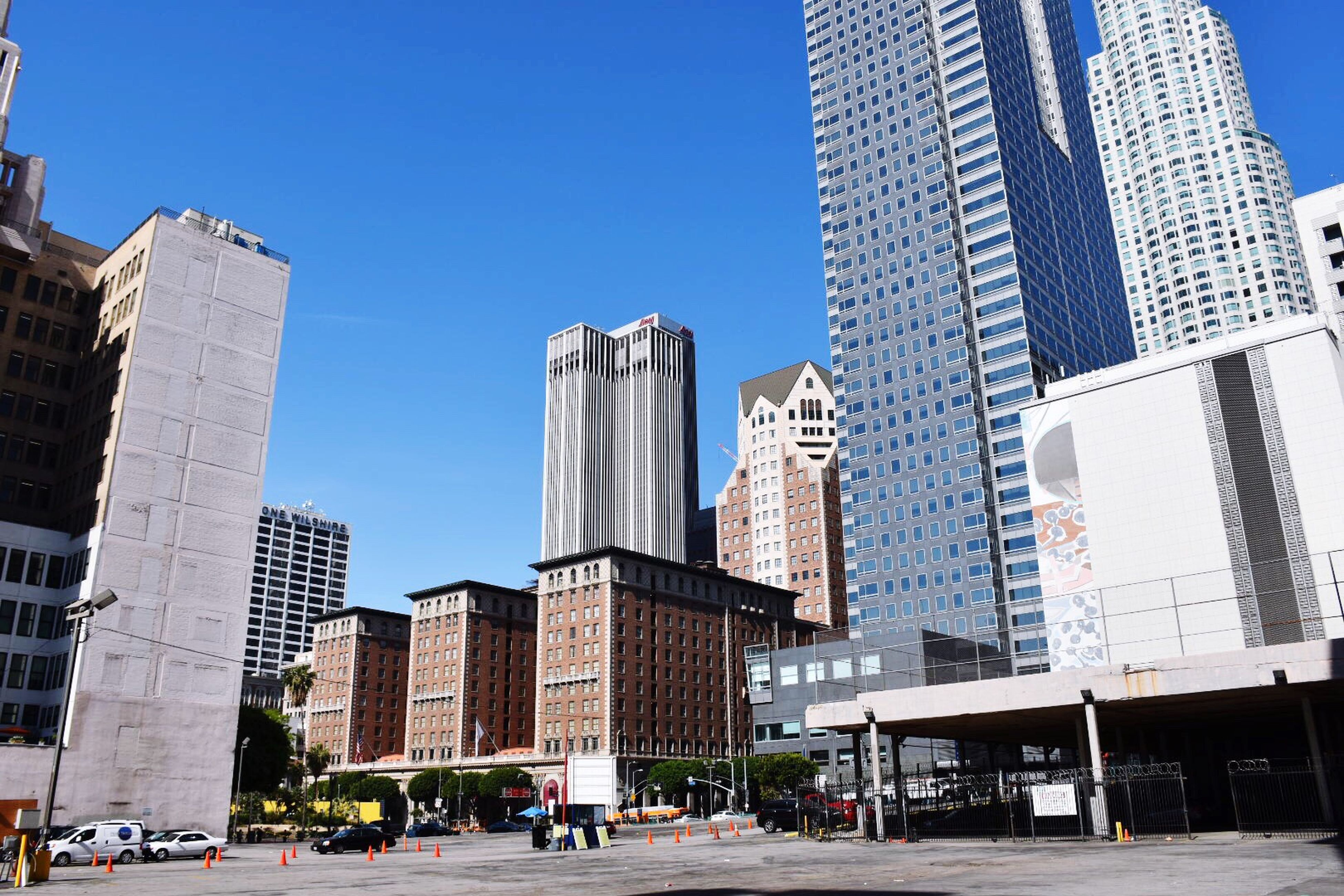 building exterior, architecture, built structure, city, clear sky, blue, skyscraper, office building, tower, tall - high, modern, sunlight, building, city life, low angle view, street, day, incidental people, copy space, road