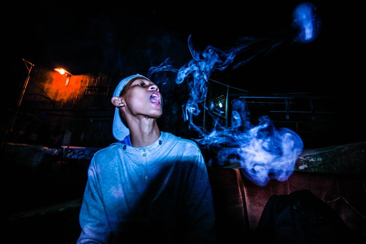 smoke - physical structure, smoking issues, smoking - activity, night, bad habit, burning, one person, addiction, real people, flame, young adult, marijuana - herbal cannabis, indoors, young women, leisure activity, lifestyles, illuminated, people, adult, one young woman only, close-up, adults only
