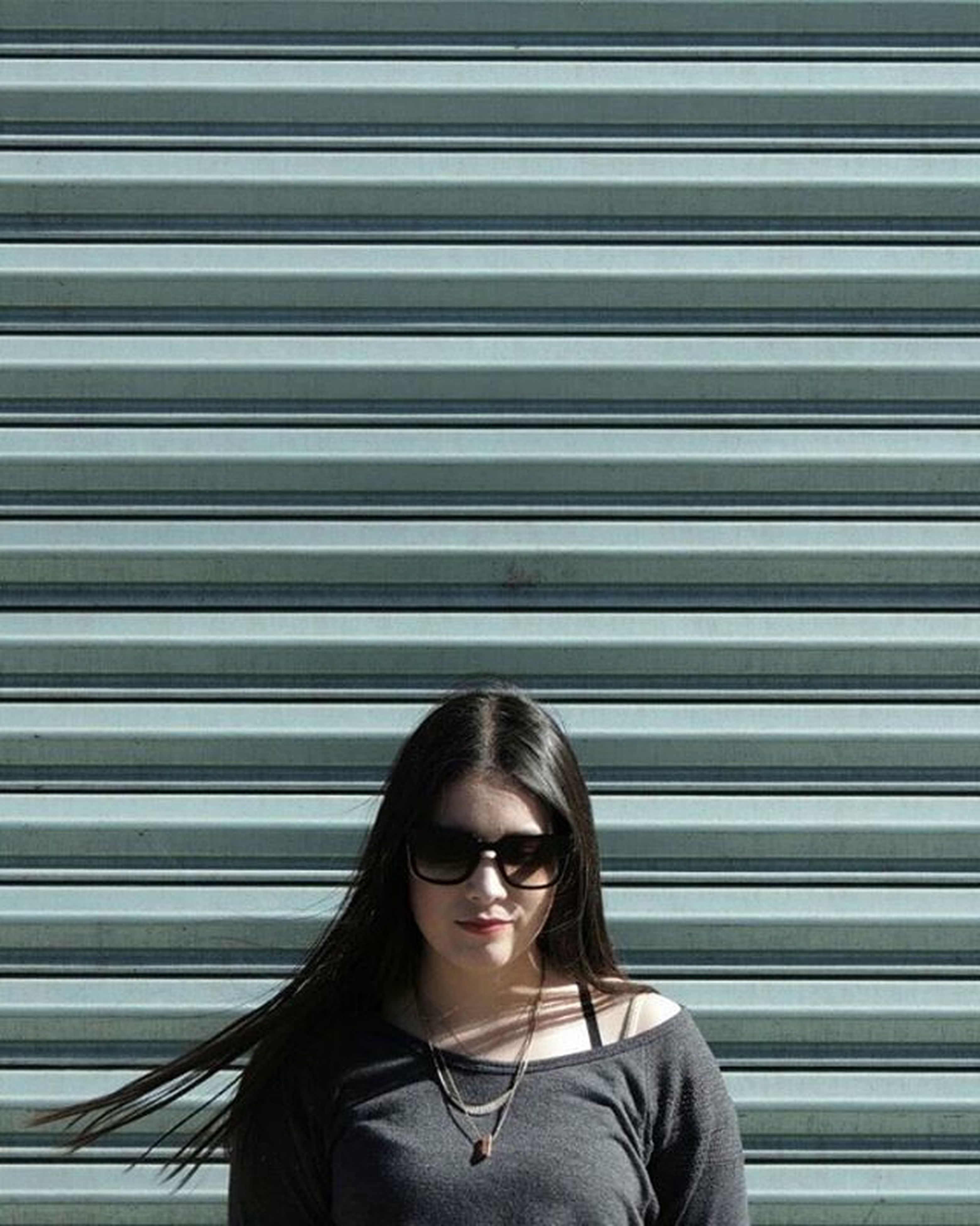 headshot, looking at camera, young adult, person, portrait, lifestyles, front view, waist up, casual clothing, leisure activity, young women, head and shoulders, built structure, focus on foreground, standing, architecture, smiling