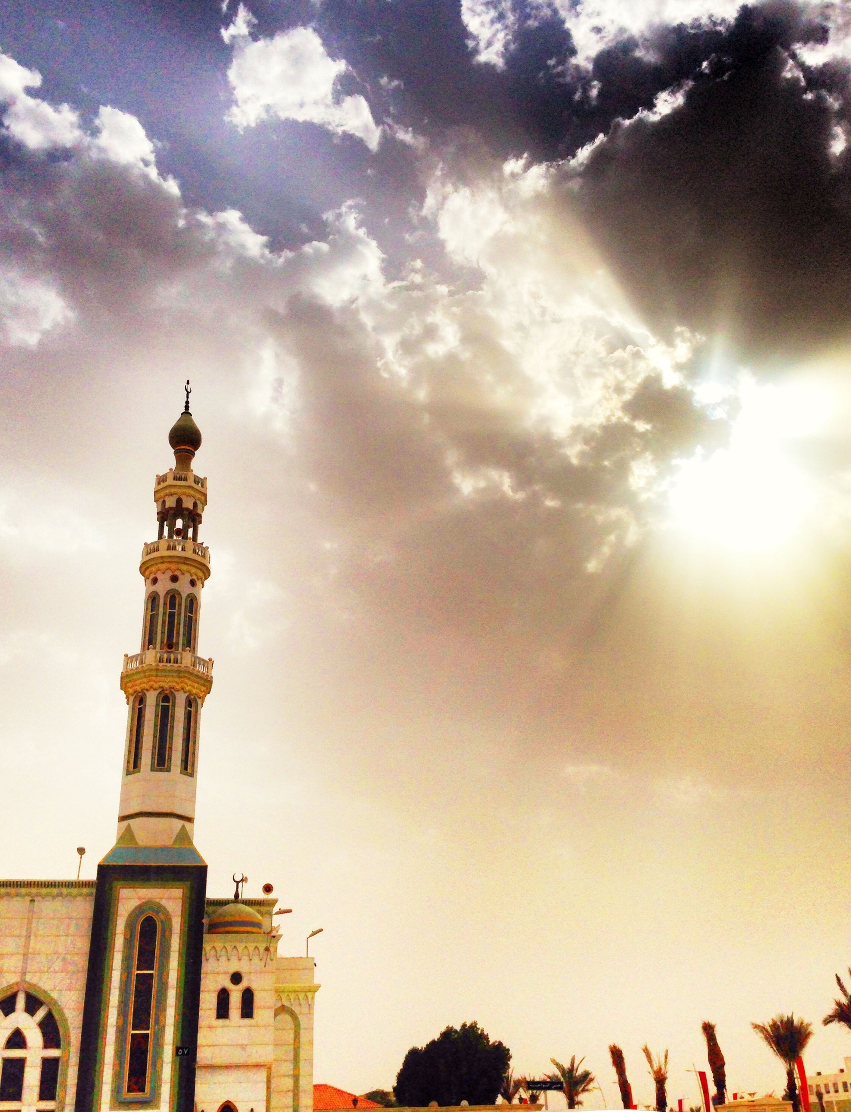 building exterior, architecture, low angle view, built structure, sky, cloud - sky, cloud, sunlight, religion, outdoors, sunset, street light, city, place of worship, high section, sun, cloudy, travel destinations, day