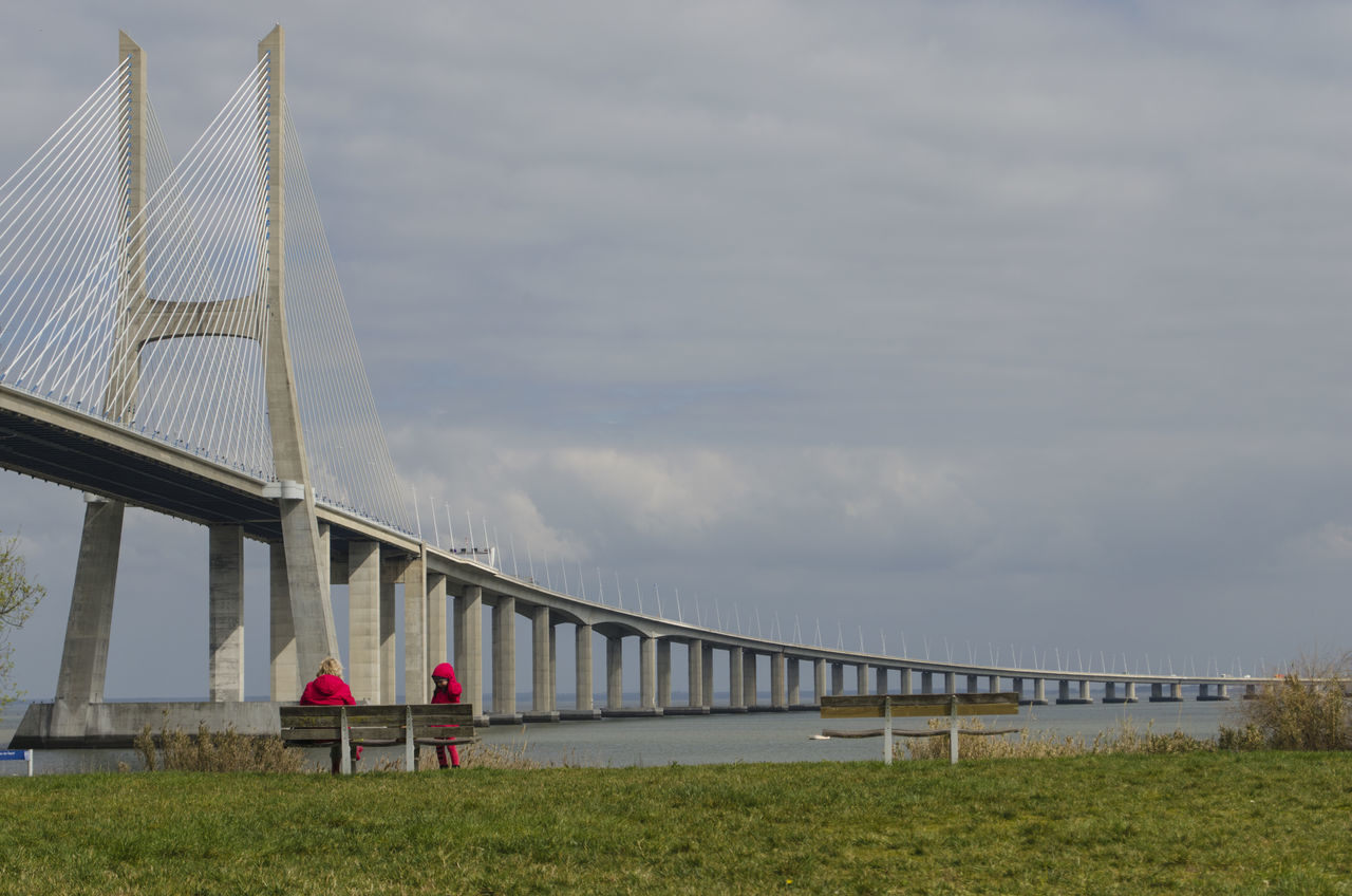 bridge - man made structure, sky, connection, outdoors, cloud - sky, built structure, day, real people, leisure activity, architecture, lifestyles, grass, two people, togetherness, nature, childhood, men, women, water, people