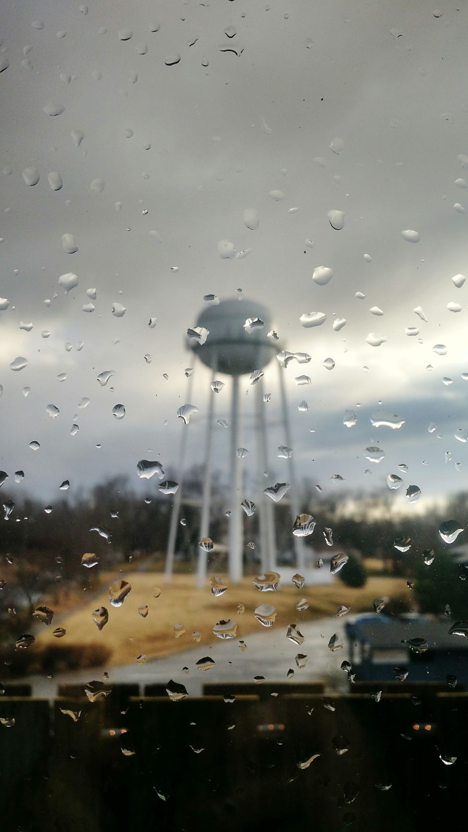 Water Droplets Cloud - Sky Wet Rainy Season Cold Temperature Small Town Small Town USA Small Town Landscape Small Town Stories Water Tower Pics Water Tower Water Tower Town Water Towers Winter Sky Window Focus On Foreground Glass Windows Complementary Colors Looking Through Window Raindrops On My Window Pane Rain On Glass Midwest Weather Winter Rain Transparent