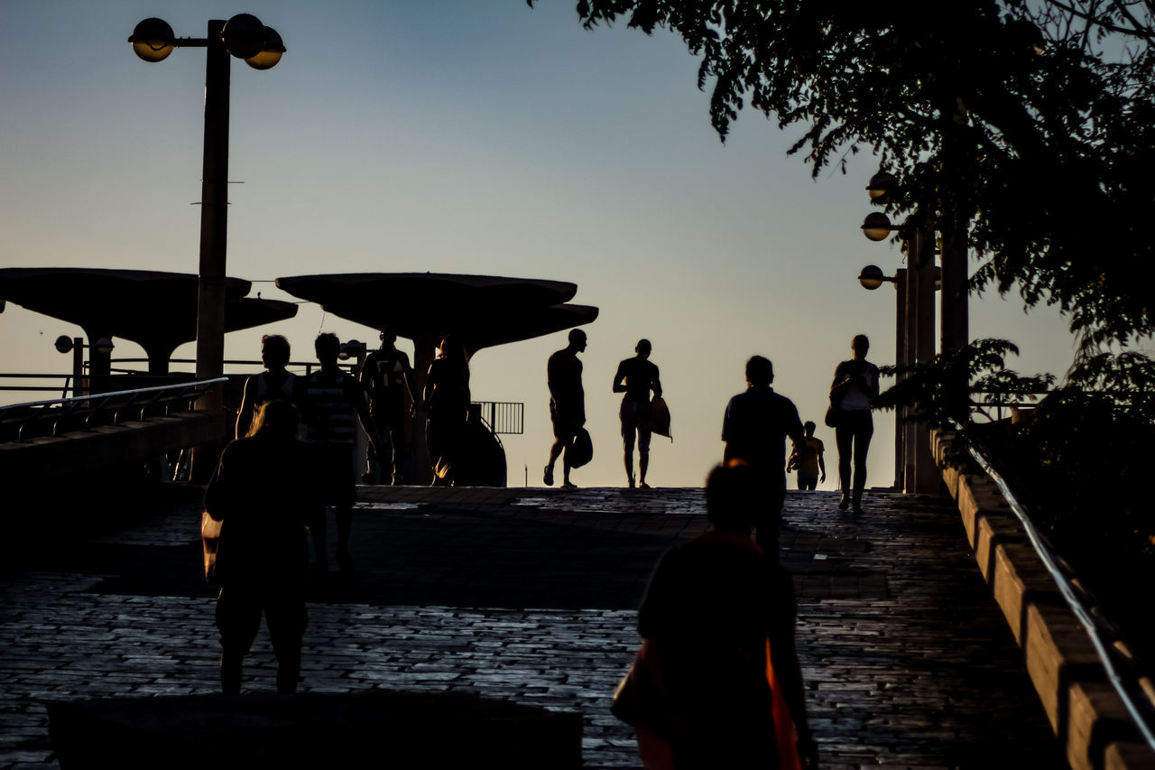 real people, silhouette, men, sunset, beach, leisure activity, outdoors, rear view, women, lifestyles, sky, travel destinations, water, standing, sea, vacations, full length, clear sky, day, tree, nature, adult, people