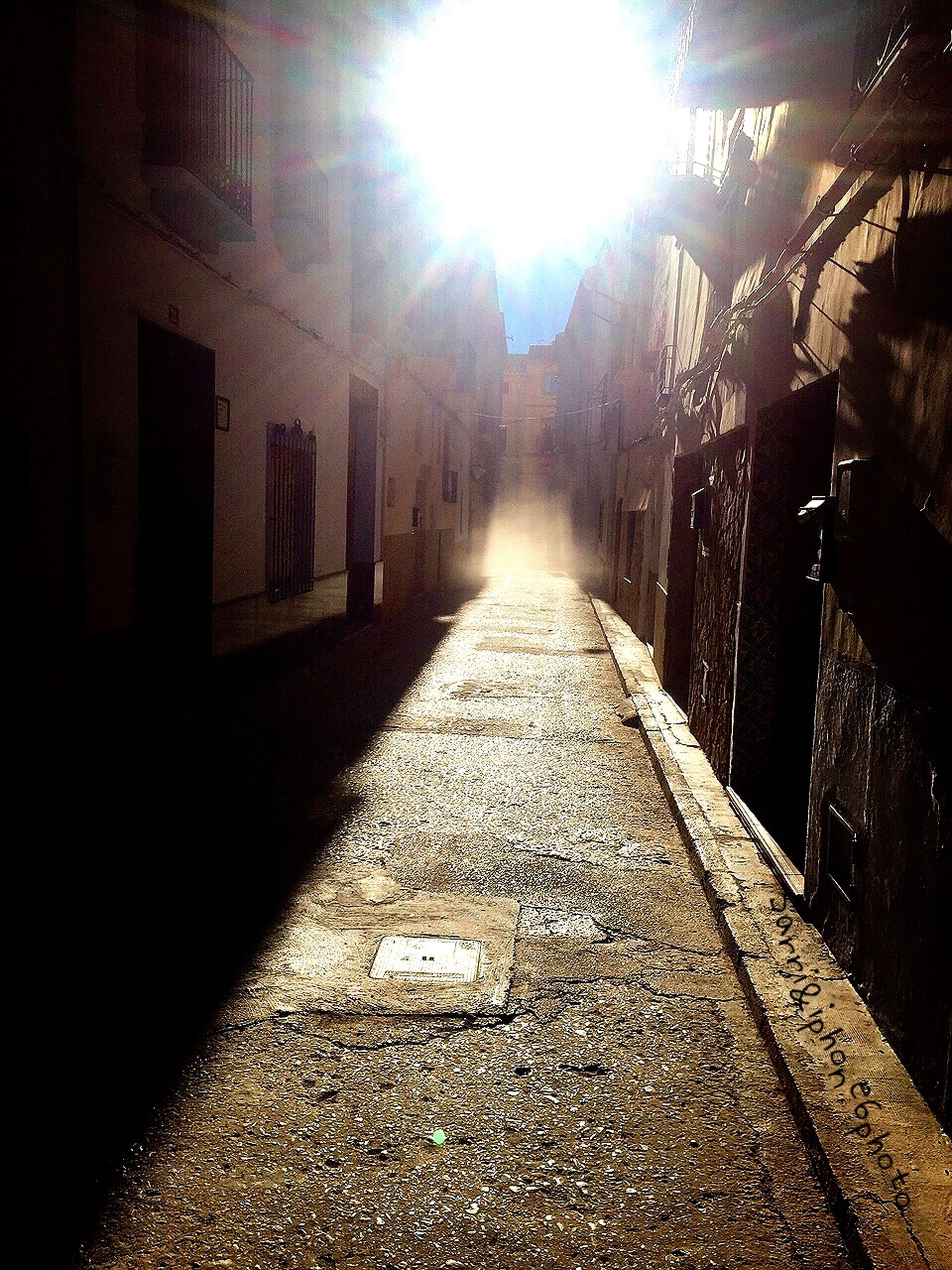 architecture, built structure, building exterior, the way forward, diminishing perspective, sunlight, city, vanishing point, street, sunbeam, building, cobblestone, lens flare, sun, residential structure, residential building, empty, shadow, narrow, sunny