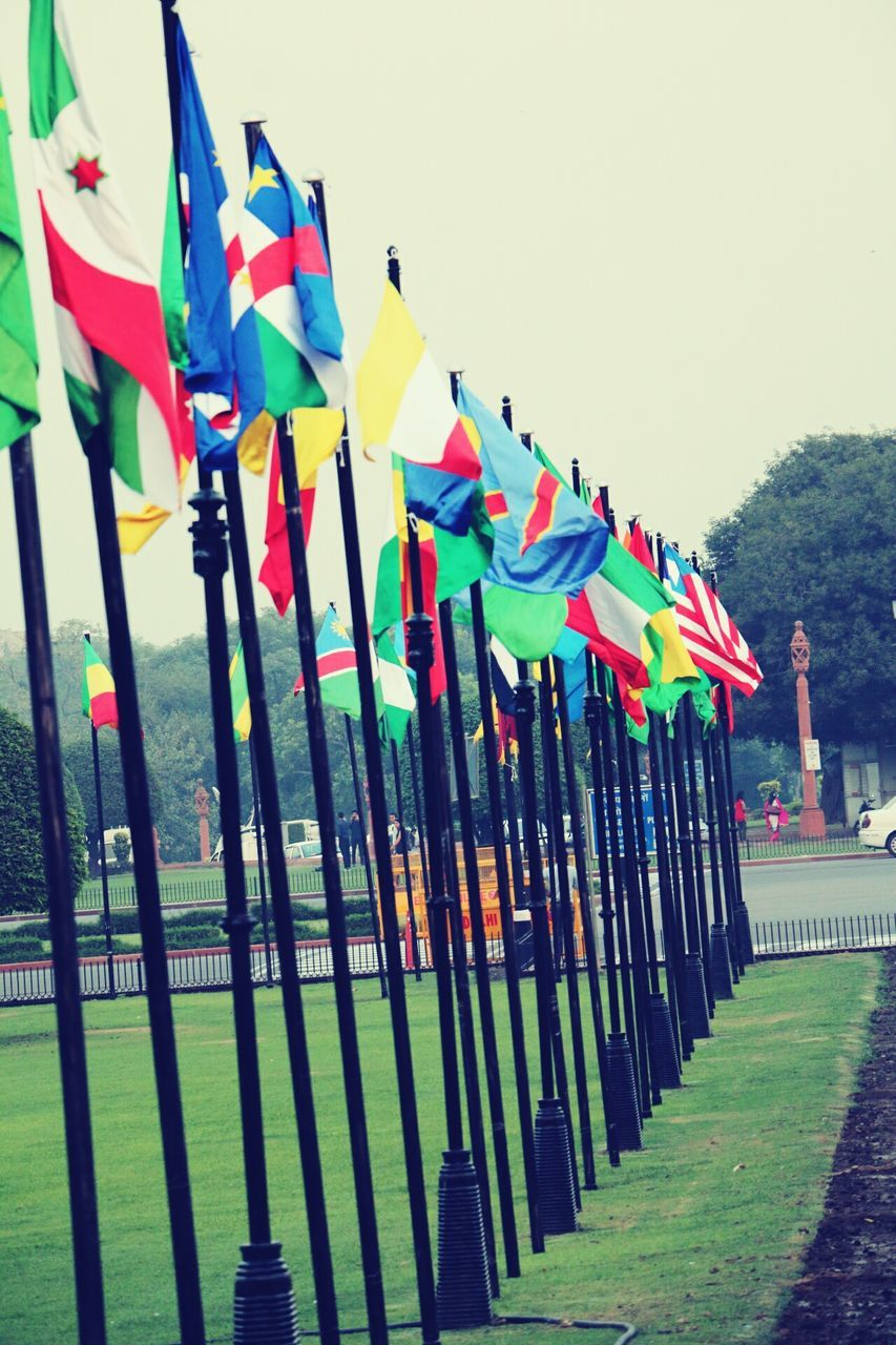 in a row, flag, multi colored, variation, large group of objects, outdoors, day, no people, clear sky, sky, hanging, grass, tree, nature