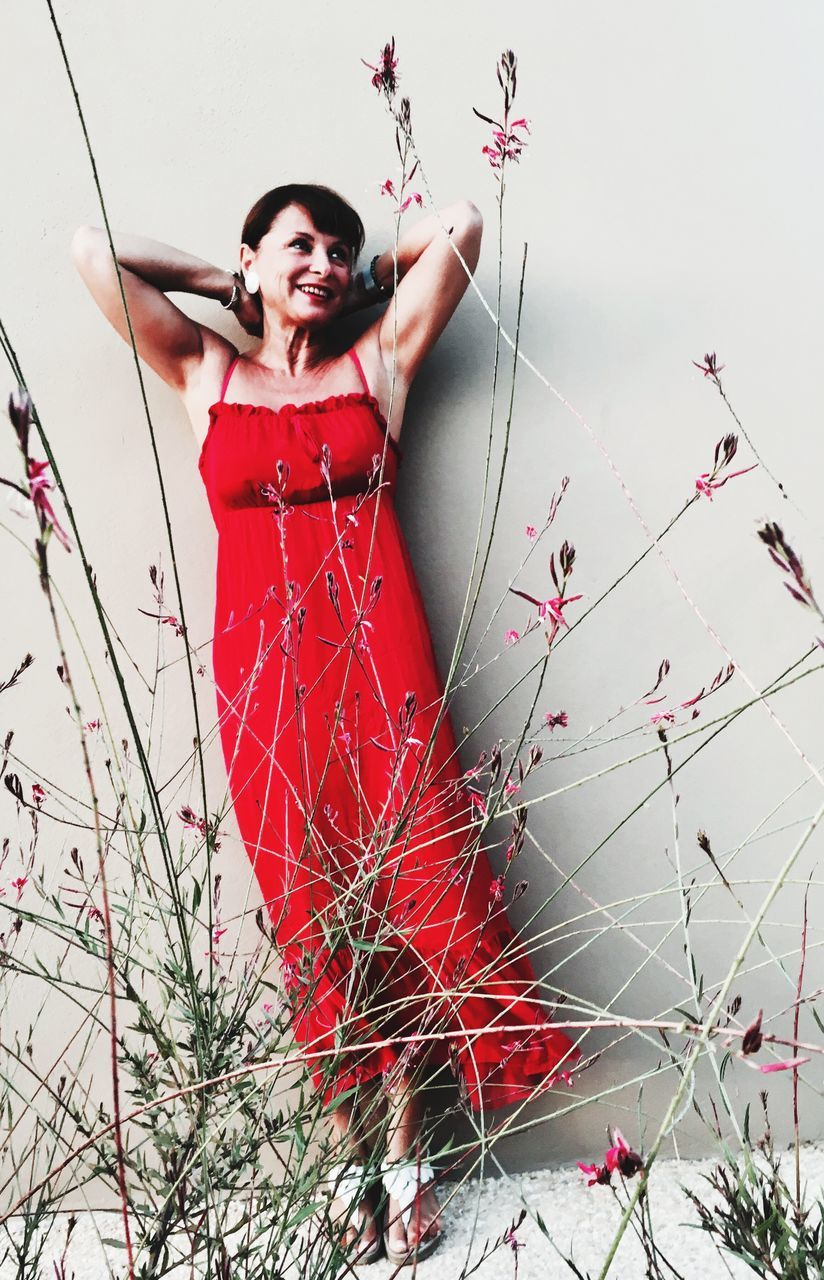 Red Dress Wearing Woman Seen Through Plants Standing Against Wall