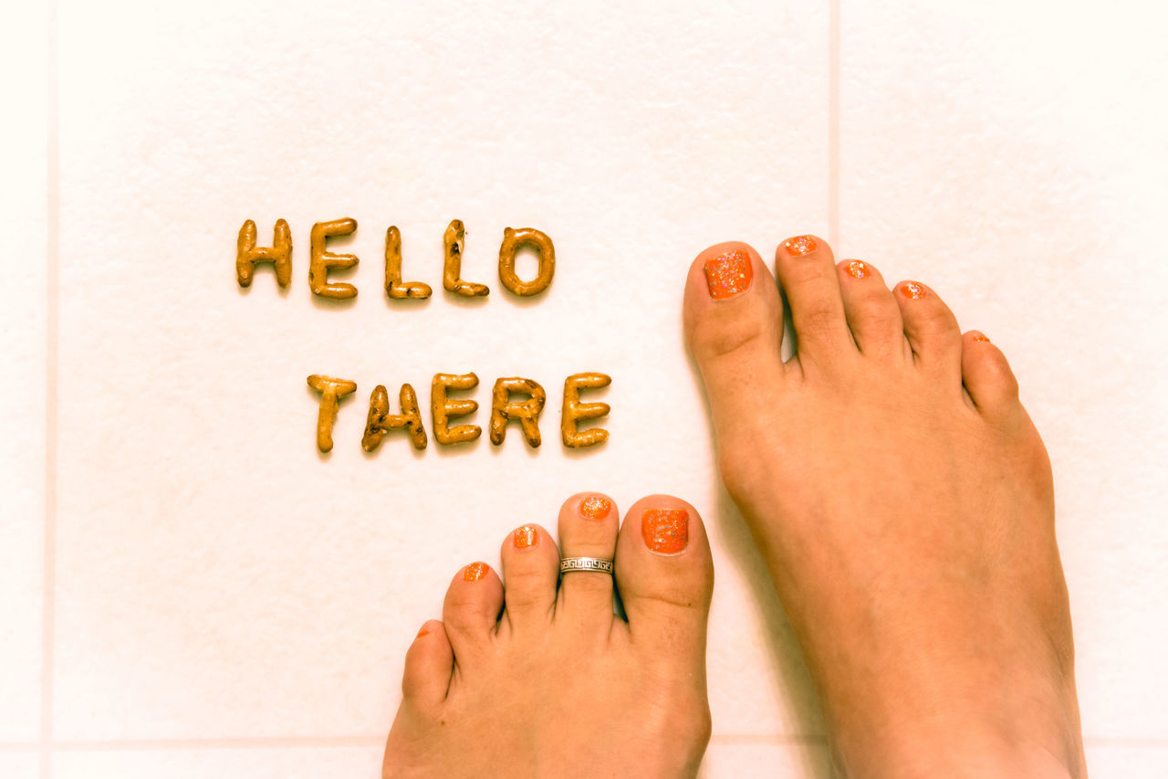 Low Section Of Woman With Hello There Text On Tiled Floor