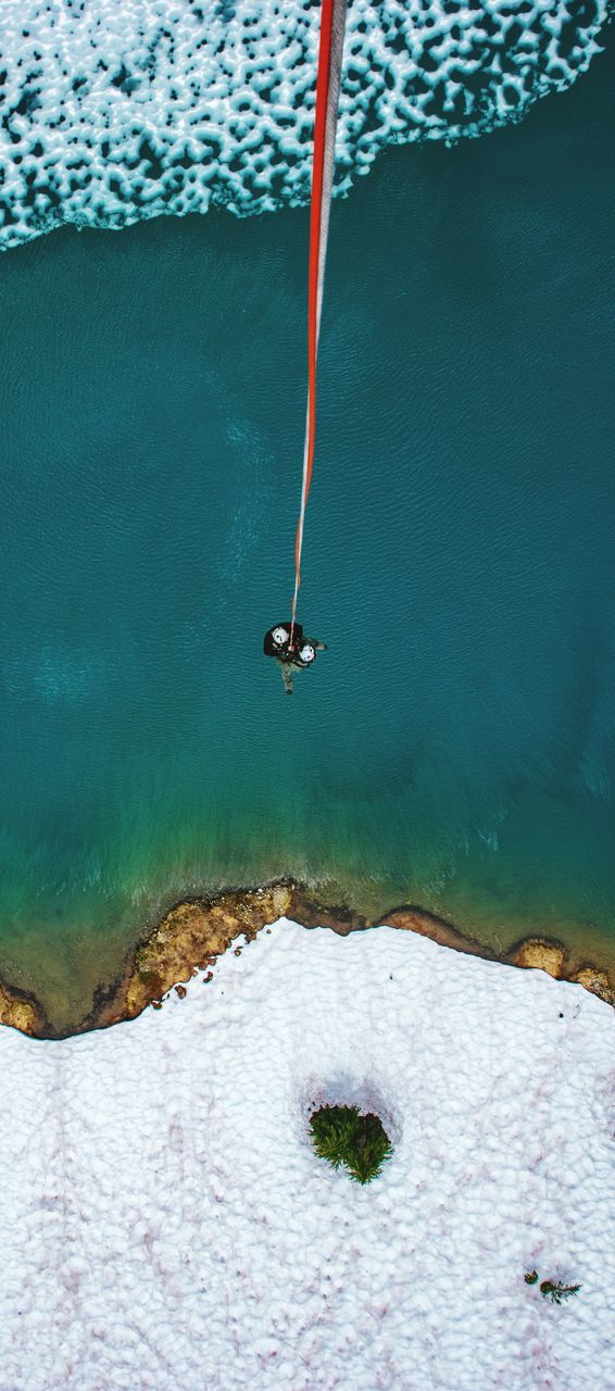 High Angle View Of Man Hanging From Rope Over Sea During Winter