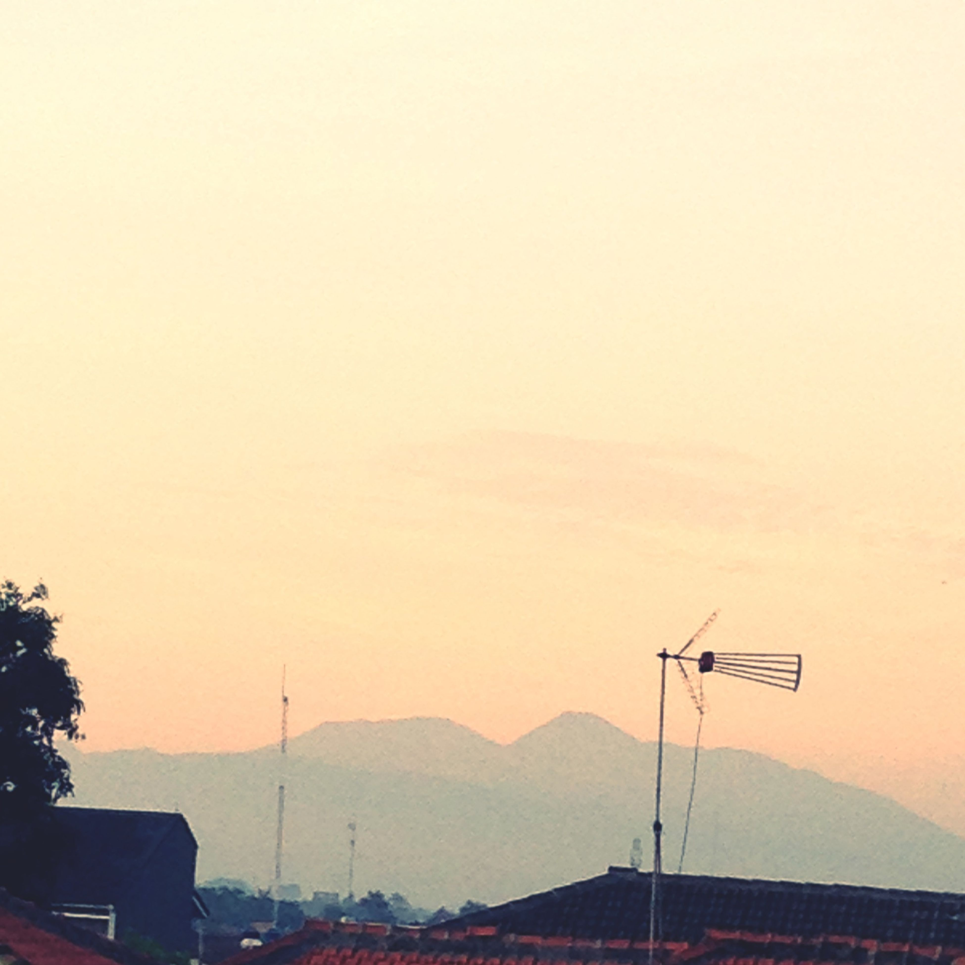copy space, sunset, mountain, clear sky, scenics, beauty in nature, tranquil scene, building exterior, nature, landscape, tranquility, sky, built structure, silhouette, orange color, architecture, outdoors, house, mountain range, no people